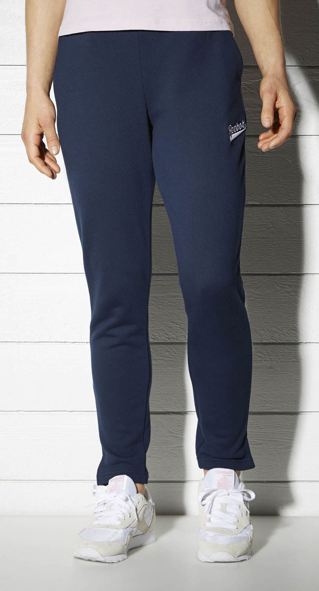 Брюки спортивные женские Reebok F Varsity Knit Pan, цвет: синий. BK2495. Размер M (46/48)BK2495Спортивные женские брюки Reebok F Varsity Knit Pan - классический стиль. Мягкая объемная ткань очень приятна на ощупь, а разрезы по бокам создают дополнительный комфорт. Элементы классического дизайна и обработка швов тесьмой придают образу законченности. Свободный крой совершенно не сковывает движения.Эластичный регулируемый пояс на шнурке.Прямой крой штанин с разрезами по бокам.Декоративная тесьма в полоску добавляет винтажные нотки.Удобные карманы по бокам.