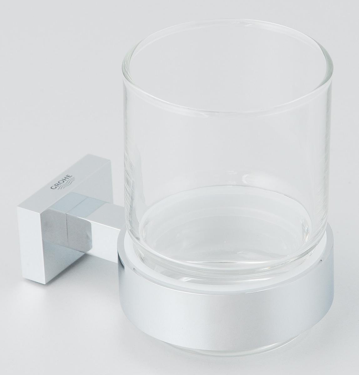 """Стакан с держателем Grohe """"Essentials Cube"""" очень практичен  и функционален. Стакан выполнен из толстого стекла.  Держатель изготовлен из металла с хромированным  покрытием. Благодаря специальной технологии Grohe  StarLight покрытие обеспечивает сияющий блеск на  протяжении всего срока службы. Кроме того, оно отталкивает  грязь, не тускнеет и обладает высокой степенью  износостойкости. Стакан крепится к стене (крепежные  элементы поставляются в комплекте). Крепление скрытое.  Благодаря неизменно актуальному дизайну и долговечному  хромированному покрытию, такой стакан отлично дополнит  интерьер ванной комнаты, воплощая собой изысканный стиль  и превосходное качество. Диаметр стакана: 7 см.  Высота стакана: 9,5 см. Размер (с держателем): 11 х 7 х 9,5 см."""