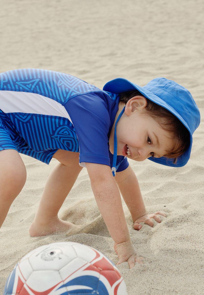 Панама детская Reima Tropical, цвет: синий. 5285316530. Размер 565285316530Защитная панама для малышей и детей постарше с фактором УФ-защиты 50+. Козырек панамы защищает лицо и глаза от вредного ультрафиолета. Изготовлена из дышащего и легкого материала SunProof. Облегченная модель без подкладки, а чтобы ветер не унес эту новую очаровательную панаму, просто завяжите завязки!