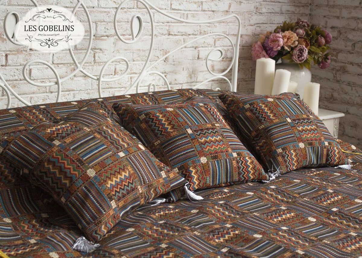 """Покрывало на кровать Les Gobelins """"Mexique"""" с ярким геометрическим рисунком привлечет к себе внимание и органично впишется в интерьер комнаты. Изделие изготовлено из высококачественной ткани гобелен и оформлено бахромой и кисточками. Необычайная красота сочетается в этом покрывале с высокой прочностью и долговечностью, а свойство гобелена по-разному проявлять себя в зависимости от освещения помещения позволяет открывать все новые и новые детали, которые, как казалось, раньше скрывал гобелен. Красочное и приятное на ощупь покрывало сделает интерьер спальни, детской или гостиной уютнее и своеобразнее.  Состав материала: 60% хлопок, 40% полиэстер."""