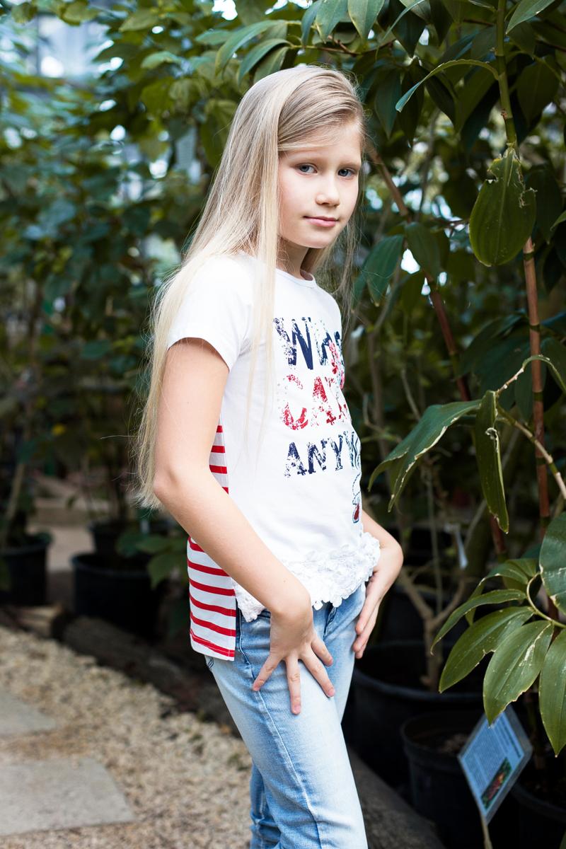 Футболка для девочки Luminoso, цвет: белый. 718098. Размер 158718098Стильная футболка из трикотажной ткани с коротким рукавом и удлиненной спинкой. Декорирована яркой аппликацией, стразами и плетеным кружевом по низу изделия.