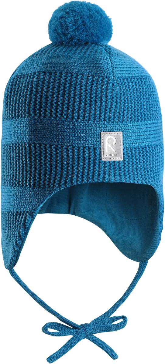 Шапка-бини детская Reima Kotka, цвет: синий. 5184296490. Размер 485184296490Красивая шерстяная шапка для малышей Reima станет отличным вариантом на зимние холода. Шапка связана из мериносовой шерсти и снабжена уютной и мягкой трикотажной подкладкой. Ветронепроницаемые вставки защищают ушки в ветреную погоду, а завязки, структурная вязка и веселый помпон завершают образ.