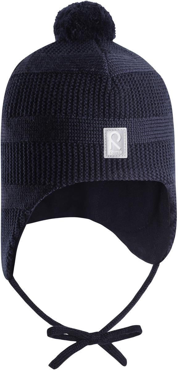Шапка-бини детская Reima Kotka, цвет: темно-синий. 5184296980. Размер 485184296980Красивая шерстяная шапка для малышей Reima станет отличным вариантом на зимние холода. Шапка связана из мериносовой шерсти и снабжена уютной и мягкой трикотажной подкладкой. Ветронепроницаемые вставки защищают ушки в ветреную погоду, а завязки, структурная вязка и веселый помпон завершают образ.