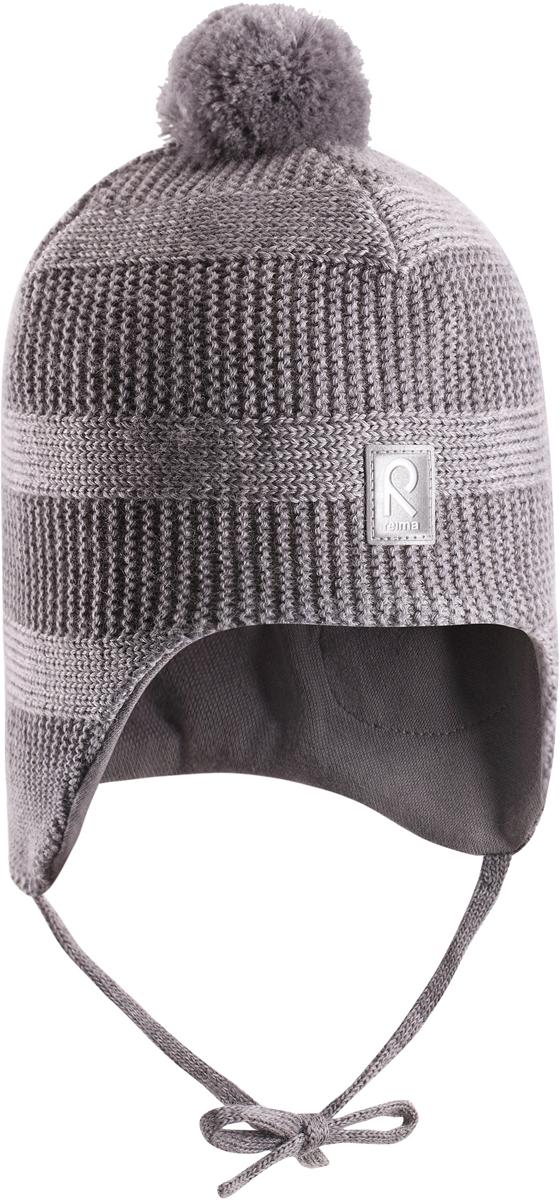 Шапка-бини детская Reima Kotka, цвет: серый. 5184299400. Размер 525184299400Красивая шерстяная шапка для малышей Reima станет отличным вариантом на зимние холода. Шапка связана из мериносовой шерсти и снабжена уютной и мягкой трикотажной подкладкой. Ветронепроницаемые вставки защищают ушки в ветреную погоду, а завязки, структурная вязка и веселый помпон завершают образ.