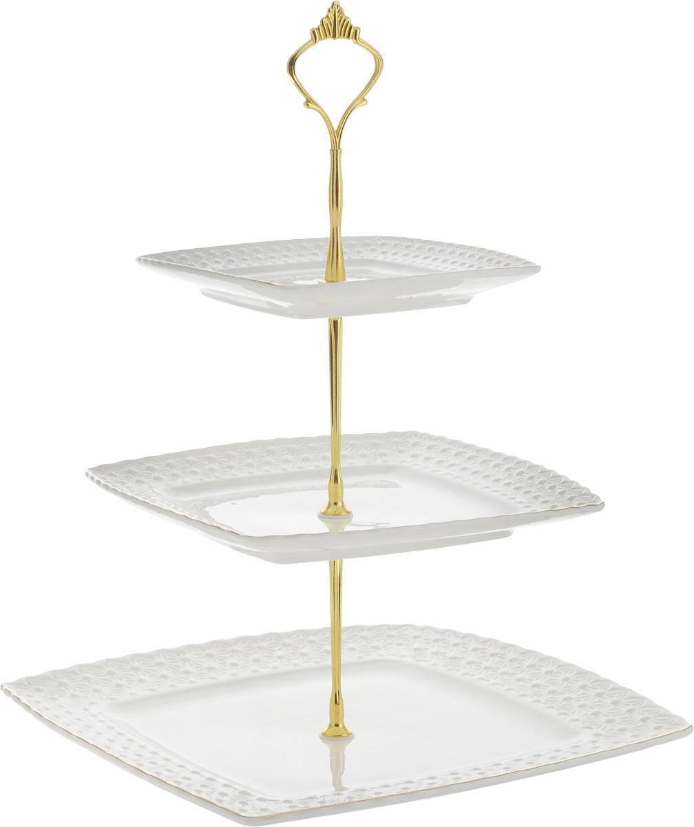 Конфетница Loraine Элис, 3-ярусная, высота 26 см. 2651226512Элегантная конфетница Loraine Элис, выполненная из керамики, сочетает в себе изысканный дизайн с максимальной функциональностью. Конфетница состоит из 3-х ярусов разного размера и предназначена для красивой сервировки конфет, фруктов и десертов. Ярусы квадратной формы оформлены оригинальным рельефным орнаментом и золотистой окантовкой. Стойка-держатель конфетницы выполнена из металла. Конфетница Loraine Элис украсит сервировку вашего стола и подчеркнет прекрасный вкус хозяина, а также станет отличным подарком.Размер большого яруса: 26 х 26 см. Размер среднего яруса: 20 х 20 см. Размер малого яруса: 15 х 15 см. Высота конфетницы: 26 см.