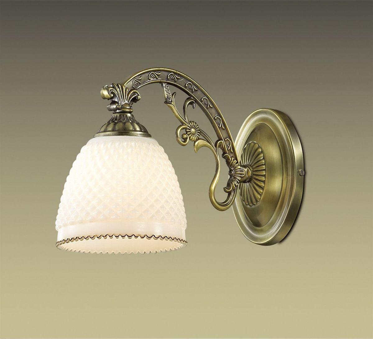 Бра Odeon Light Masala, 1 х E14, 40W. 2868/1W2868/1WИтальянские мастера по производству светотехники славятся крайне ответственным отношением к качеству и долговечности выпускаемой продукции. Использование только лучших материалов и тщательная проверка всех изделий исключает выпуск товаров ненадлежащего качества. Одним из наглядных примеров эффективности такого подхода является настенное бра Odeon Light Masala. Данный светильник сочетает в себе не только отличные технические характеристики и аккуратность исполнения, но и оригинальность внешнего вида. Дизайн конструкции выполнен с использованием форм и цветов, характерных для стиля классика. Изготовленный из металла корпус бронзового цвета органично сочетается с плафоном из стекла. Нельзя не сказать и о прекрасной функциональности данного бра. Благодаря достаточно высокой мощности в 40 Вт, светильник способен освещать пространство площадью до 2,2 кв.м. Используя бра Odeon Light Masala, можно создать уютный и комфортный уголок для полноценного отдыха, тихих вечеров в компании с увлекательной книгой, занятий творчеством или продуктивной работы. Изделие прекрасно подойдет для размещения в гостиной, прихожей или спальне и будет многие годы радовать вас надежным освещением и своим симпатичным внешним видом.