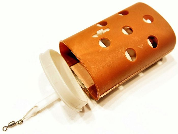 Кормушка для рыб Stonfo, цвет: коричневый, 50 г179Кормушка Stonfo с утяжелителем изготовлена из полипропилена. Кормушка оснащена дверцей, которую можно открывать и закрывать при необходимости. Предназначена для использования прикорма с живыми насадками, которые в последствии выползают через открывающиеся отверстия.