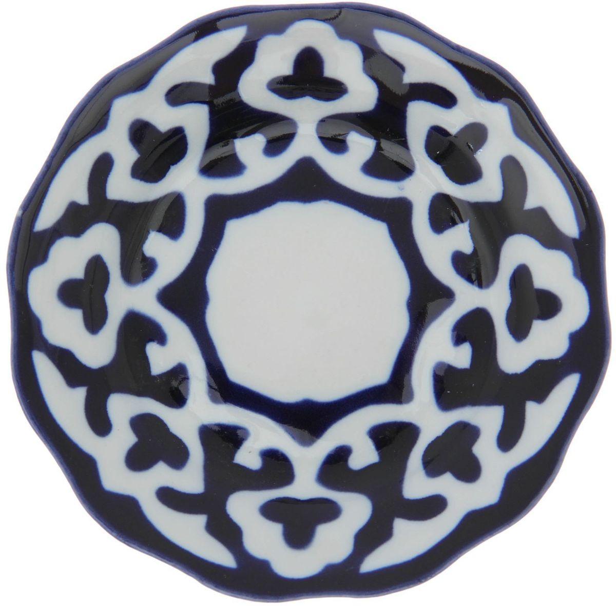 Тарелка Turon Porcelain Пахта, цвет: белый, синий, диаметр 12,5 см1386442Узбекская посуда известна всему миру уже более тысячи лет. Ей любовались царские особы, на ней подавали еду для шейхов и знатных персон. Формулы красок и глазури передаются из поколения в поколение. По сей день качественные расписные изделия продолжают восхищать совершенством и завораживающей красотой.Тарелка Turon Porcelain Пахта подойдет для повседневной и праздничной сервировки. Дополните стол текстилем и салфетками в тон, чтобы получить элегантное убранство с яркими акцентами.Национальная узбекская роспись Пахта сдержанна и благородна. Витиеватые узоры выводятся тонкой кистью, а фон заливается кобальтом. Синий краситель при обжиге слегка растекается и придает контуру изображений голубой оттенок. Густая глазурь наносится толстым слоем, благодаря чему рисунок мерцает.