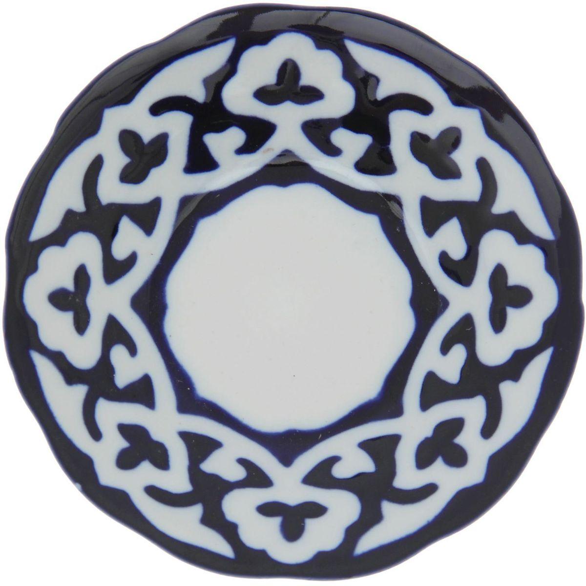 Тарелка Turon Porcelain Пахта, цвет: синий, белый, диаметр 13 см1386443Узбекская посуда известна всему миру уже более тысячи лет. Ей любовались царские особы, на ней подавали еду для шейхов и знатных персон. Формулы красок и глазури передаются из поколения в поколение. По сей день качественные расписные изделия продолжают восхищать совершенством и завораживающей красотой. Тарелка Turon Porcelain Пахта подойдет для повседневной и праздничной сервировки. Дополните стол текстилем и салфетками в тон, чтобы получить элегантное убранство с яркими акцентами. Национальная узбекская роспись Пахта сдержанна и благородна. Витиеватые узоры выводятся тонкой кистью, а фон заливается кобальтом. Синий краситель при обжиге слегка растекается и придает контуру изображений голубой оттенок. Густая глазурь наносится толстым слоем, благодаря чему рисунок мерцает.