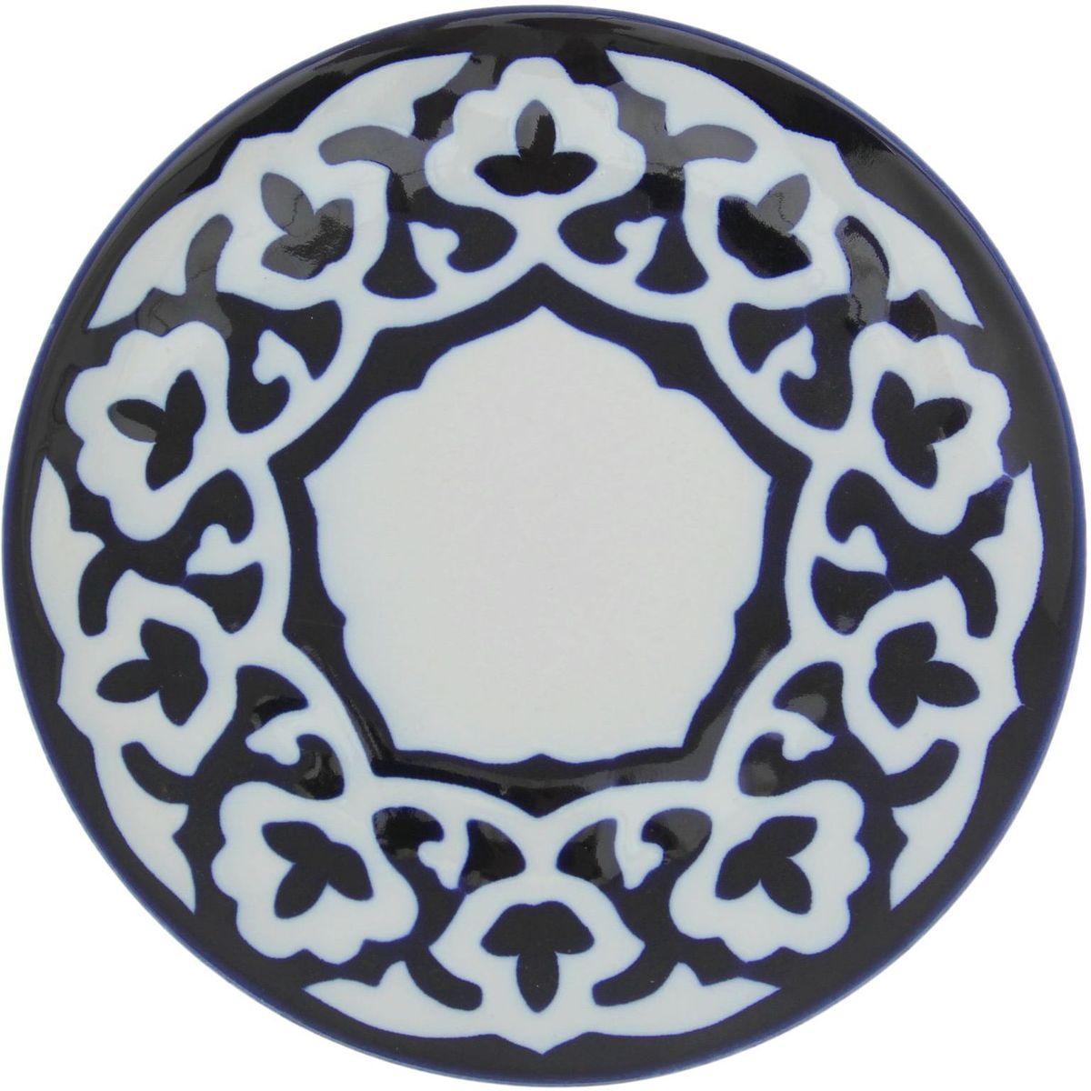 Тарелка Turon Porcelain Пахта, цвет: белый, синий, диаметр 19,5 см1386446Узбекская посуда известна всему миру уже более тысячи лет. Ей любовались царские особы, на ней подавали еду для шейхов и знатных персон. Формулы красок и глазури передаются из поколения в поколение. По сей день качественные расписные изделия продолжают восхищать совершенством и завораживающей красотой. Тарелка Turon Porcelain Пахта подойдет для повседневной и праздничной сервировки. Дополните стол текстилем и салфетками в тон, чтобы получить элегантное убранство с яркими акцентами. Национальная узбекская роспись Пахта сдержанна и благородна. Витиеватые узоры выводятся тонкой кистью, а фон заливается кобальтом. Синий краситель при обжиге слегка растекается и придает контуру изображений голубой оттенок. Густая глазурь наносится толстым слоем, благодаря чему рисунок мерцает.
