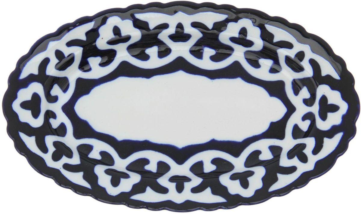 Тарелка Turon Porcelain Пахта, цвет: белый, синий, 23 х 14 см1386448Узбекская посуда известна всему миру уже более тысячи лет. Ей любовались царские особы, на ней подавали еду для шейхов и знатных персон. Формулы красок и глазури передаются из поколения в поколение. По сей день качественные расписные изделия продолжают восхищать совершенством и завораживающей красотой.Тарелка Turon Porcelain Пахта подойдет для повседневной и праздничной сервировки. Дополните стол текстилем и салфетками в тон, чтобы получить элегантное убранство с яркими акцентами.Национальная узбекская роспись Пахта сдержанна и благородна. Витиеватые узоры выводятся тонкой кистью, а фон заливается кобальтом. Синий краситель при обжиге слегка растекается и придает контуру изображений голубой оттенок. Густая глазурь наносится толстым слоем, благодаря чему рисунок мерцает.