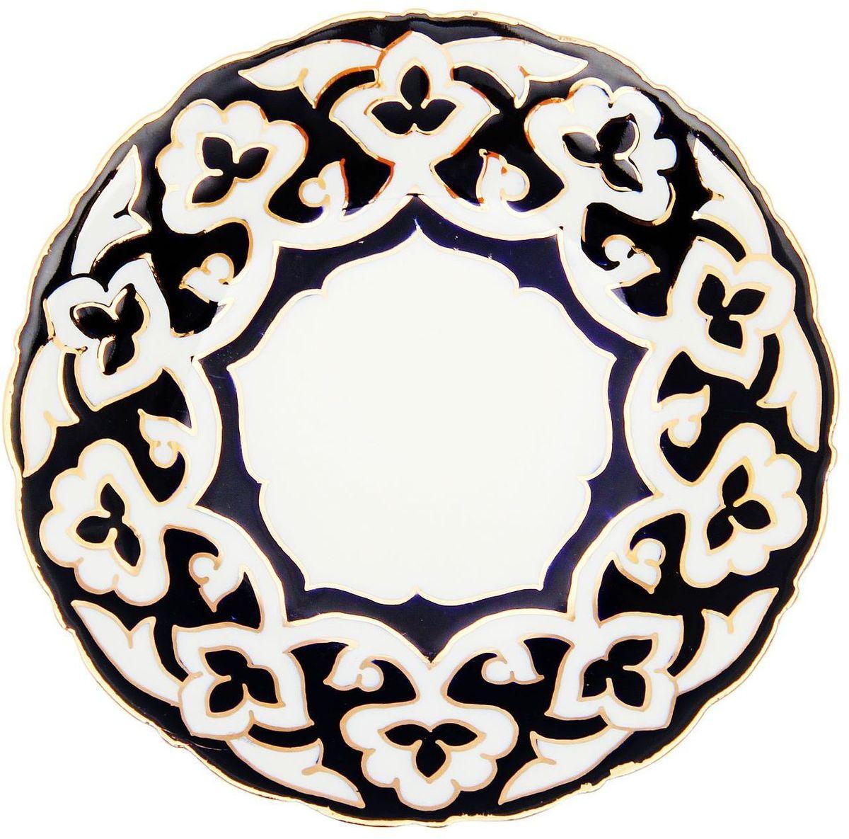 Тарелка Turon Porcelain Пахта, цвет: белый, синий, золотистый, диаметр 16 см1625355Узбекская посуда известна всему миру уже более тысячи лет. Ей любовались царские особы, на ней подавали еду для шейхов и знатных персон. Формулы красок и глазури передаются из поколения в поколение. По сей день качественные расписные изделия продолжают восхищать совершенством и завораживающей красотой. Тарелка Turon Porcelain Пахта подойдет для повседневной и праздничной сервировки. Дополните стол текстилем и салфетками в тон, чтобы получить элегантное убранство с яркими акцентами. Национальная узбекская роспись Пахта сдержанна и благородна. Витиеватые узоры выводятся тонкой кистью, а фон заливается кобальтом. Синий краситель при обжиге слегка растекается и придает контуру изображений голубой оттенок. Густая глазурь наносится толстым слоем, благодаря чему рисунок мерцает.