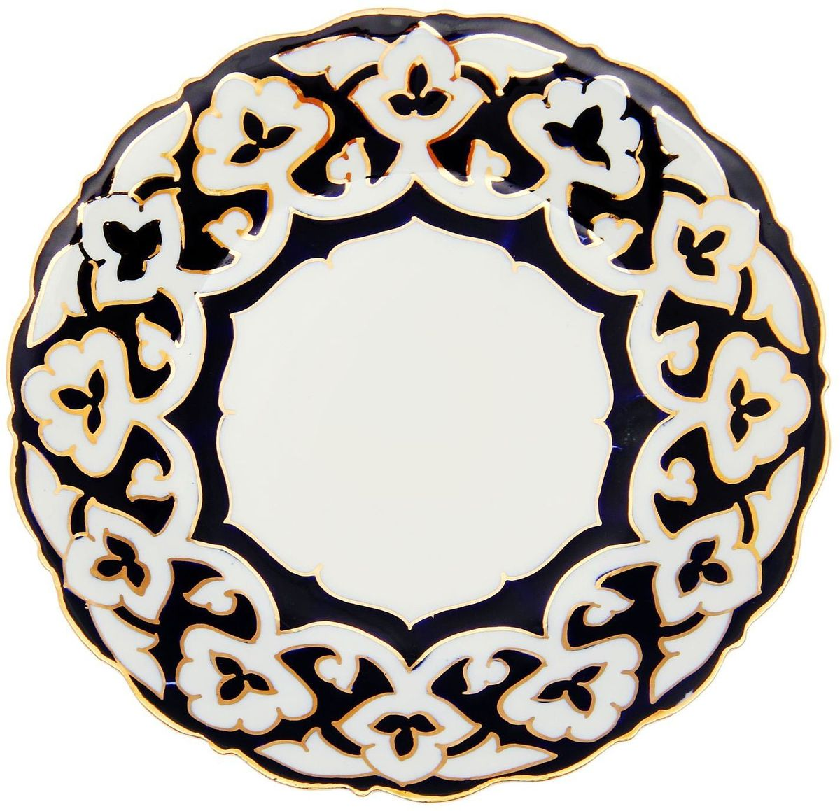 Тарелка Turon Porcelain Пахта, цвет: белый, синий, золотистый, диаметр 17,5 см96551Узбекская посуда известна всему миру уже более тысячи лет. Ей любовались царские особы, на ней подавали еду для шейхов и знатных персон. Формулы красок и глазури передаются из поколения в поколение. По сей день качественные расписные изделия продолжают восхищать совершенством и завораживающей красотой.Тарелка Turon Porcelain Пахта подойдет для повседневной и праздничной сервировки. Дополните стол текстилем и салфетками в тон, чтобы получить элегантное убранство с яркими акцентами.Национальная узбекская роспись Пахта сдержанна и благородна. Витиеватые узоры выводятся тонкой кистью, а фон заливается кобальтом. Синий краситель при обжиге слегка растекается и придает контуру изображений голубой оттенок. Густая глазурь наносится толстым слоем, благодаря чему рисунок мерцает.