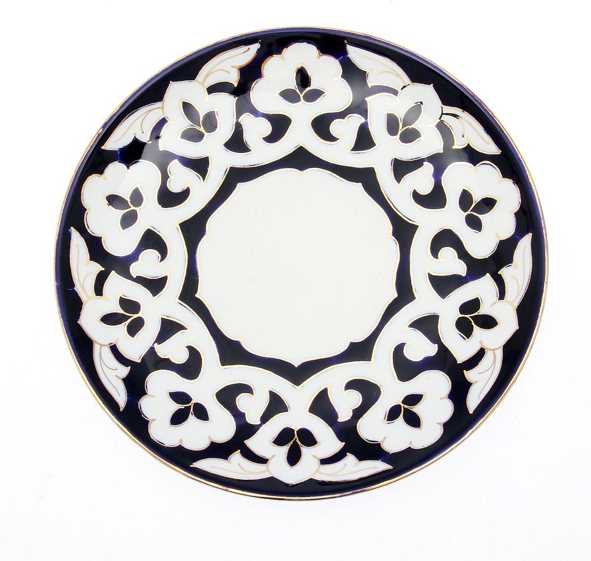 Тарелка Turon Porcelain Пахта, цвет: белый, синий, золотистый, диаметр 22,5 см1625358Узбекская посуда известна всему миру уже более тысячи лет. Ей любовались царские особы, на ней подавали еду для шейхов и знатных персон. Формулы красок и глазури передаются из поколения в поколение. По сей день качественные расписные изделия продолжают восхищать совершенством и завораживающей красотой. Тарелка Turon Porcelain Пахта подойдет для повседневной и праздничной сервировки. Дополните стол текстилем и салфетками в тон, чтобы получить элегантное убранство с яркими акцентами. Национальная узбекская роспись Пахта сдержанна и благородна. Витиеватые узоры выводятся тонкой кистью, а фон заливается кобальтом. Синий краситель при обжиге слегка растекается и придает контуру изображений голубой оттенок. Густая глазурь наносится толстым слоем, благодаря чему рисунок мерцает.