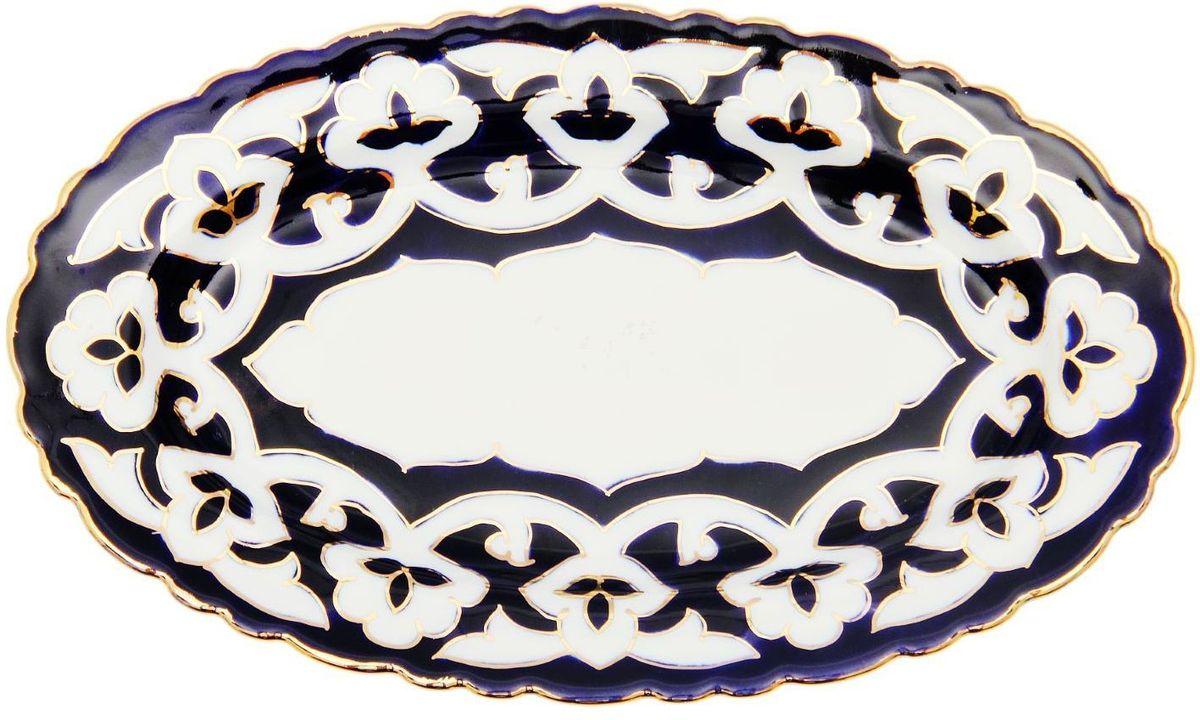 Тарелка Turon Porcelain Пахта, цвет: белый, синий, золотистый, 23 х 14 см1625359Узбекская посуда известна всему миру уже более тысячи лет. Ей любовались царские особы, на ней подавали еду для шейхов и знатных персон. Формулы красок и глазури передаются из поколения в поколение. По сей день качественные расписные изделия продолжают восхищать совершенством и завораживающей красотой. Тарелка Turon Porcelain Пахта подойдет для повседневной и праздничной сервировки. Дополните стол текстилем и салфетками в тон, чтобы получить элегантное убранство с яркими акцентами. Национальная узбекская роспись Пахта сдержанна и благородна. Витиеватые узоры выводятся тонкой кистью, а фон заливается кобальтом. Синий краситель при обжиге слегка растекается и придает контуру изображений голубой оттенок. Густая глазурь наносится толстым слоем, благодаря чему рисунок мерцает.