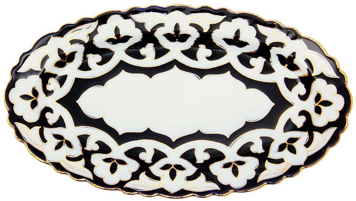 Тарелка Turon Porcelain Пахта, цвет: синий, белый, золотистый, 30 х 17 см1625360Узбекская посуда известна всему миру уже более тысячи лет. Ей любовались царские особы, на ней подавали еду для шейхов и знатных персон. Формулы красок и глазури передаются из поколения в поколение. По сей день качественные расписные изделия продолжают восхищать совершенством и завораживающей красотой. Тарелка Turon Porcelain Пахта подойдет для повседневной и праздничной сервировки. Дополните стол текстилем и салфетками в тон, чтобы получить элегантное убранство с яркими акцентами. Национальная узбекская роспись Пахта сдержанна и благородна. Витиеватые узоры выводятся тонкой кистью, а фон заливается кобальтом. Синий краситель при обжиге слегка растекается и придает контуру изображений голубой оттенок. Густая глазурь наносится толстым слоем, благодаря чему рисунок мерцает.