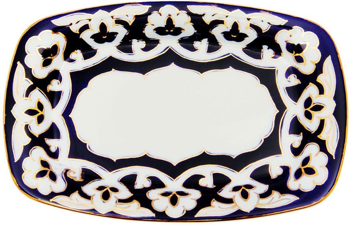 Тарелка Turon Porcelain Пахта, цвет: синий, белый, золотистый, 25 х 23 см1625361Узбекская посуда известна всему миру уже более тысячи лет. Ей любовались царские особы, на ней подавали еду для шейхов и знатных персон. Формулы красок и глазури передаются из поколения в поколение. По сей день качественные расписные изделия продолжают восхищать совершенством и завораживающей красотой.Тарелка Turon Porcelain Пахта подойдет для повседневной и праздничной сервировки. Дополните стол текстилем и салфетками в тон, чтобы получить элегантное убранство с яркими акцентами.Национальная узбекская роспись Пахта сдержанна и благородна. Витиеватые узоры выводятся тонкой кистью, а фон заливается кобальтом. Синий краситель при обжиге слегка растекается и придает контуру изображений голубой оттенок. Густая глазурь наносится толстым слоем, благодаря чему рисунок мерцает.