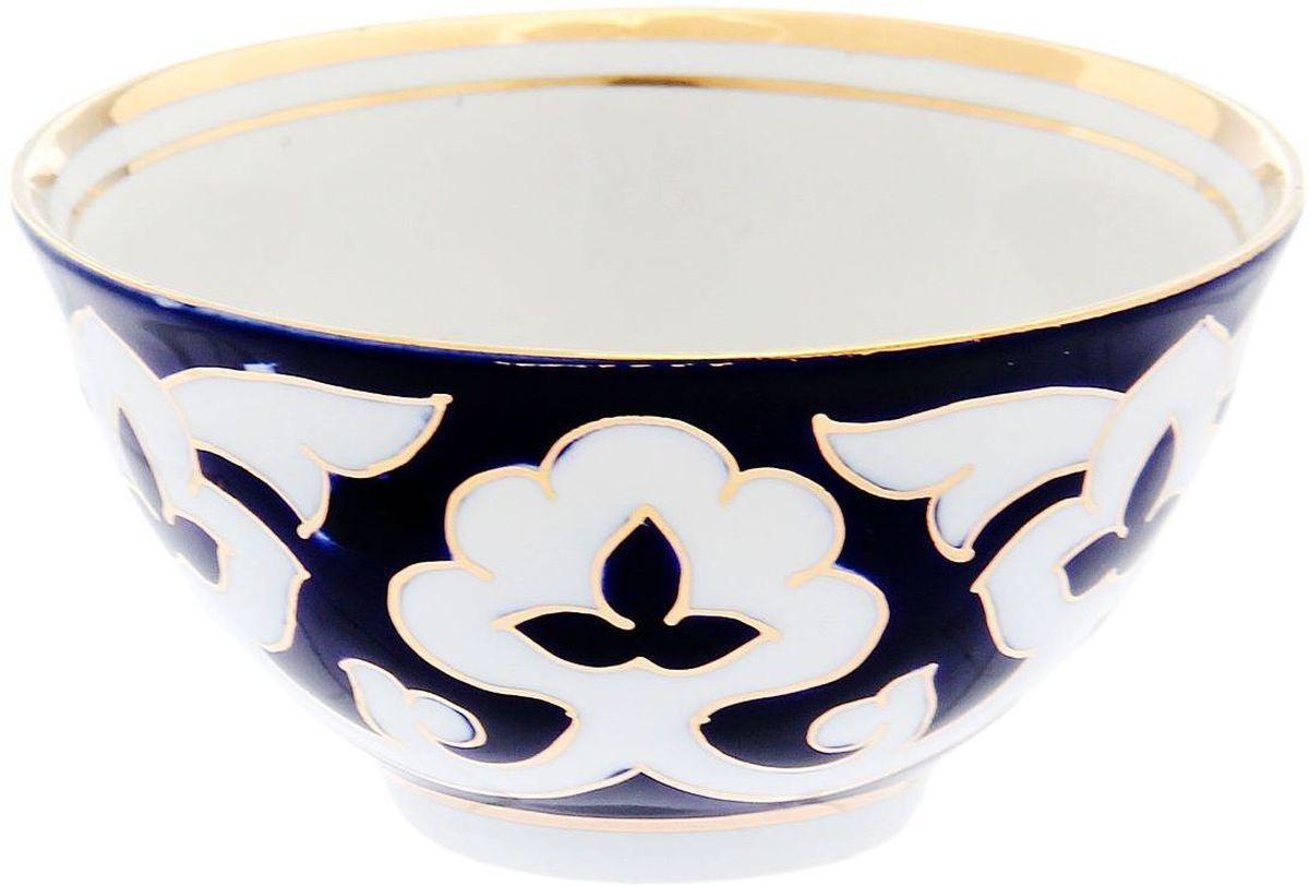 Пиала Turon Porcelain Пахта, цвет: синий, белый, золотистый, 250 мл1625367Узбекская посуда известна всему миру уже более тысячи лет. Ей любовались царские особы, на ней подавали еду для шейхов и знатных персон. Формулы красок и глазури передаются из поколения в поколение. По сей день качественные расписные изделия продолжают восхищать совершенством и завораживающей красотой.Данный предмет подойдёт для повседневной и праздничной сервировки. Дополните стол текстилем и салфетками в тон, чтобы получить элегантное убранство с яркими акцентами.Национальная узбекская роспись «Пахта» сдержанна и благородна. Витиеватые узоры выводятся тонкой кистью, а фон заливается кобальтом. Синий краситель при обжиге слегка растекается и придаёт контуру изображений голубой оттенок. Густая глазурь наносится толстым слоем, благодаря чему рисунок мерцает.
