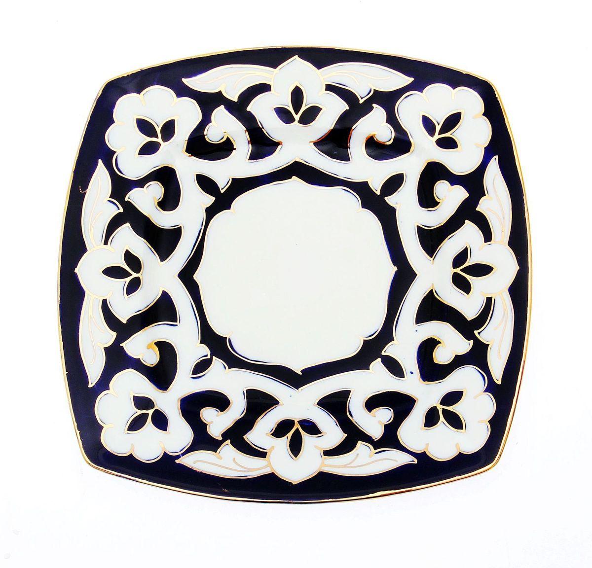 Тарелка Turon Porcelain Пахта, цвет: синий, белый, золотистый, 20 х 20 см1625376Узбекская посуда известна всему миру уже более тысячи лет. Ей любовались царские особы, на ней подавали еду для шейхов и знатных персон. Формулы красок и глазури передаются из поколения в поколение. По сей день качественные расписные изделия продолжают восхищать совершенством и завораживающей красотой. Тарелка Turon Porcelain Пахта подойдет для повседневной и праздничной сервировки. Дополните стол текстилем и салфетками в тон, чтобы получить элегантное убранство с яркими акцентами. Национальная узбекская роспись Пахта сдержанна и благородна. Витиеватые узоры выводятся тонкой кистью, а фон заливается кобальтом. Синий краситель при обжиге слегка растекается и придает контуру изображений голубой оттенок. Густая глазурь наносится толстым слоем, благодаря чему рисунок мерцает.