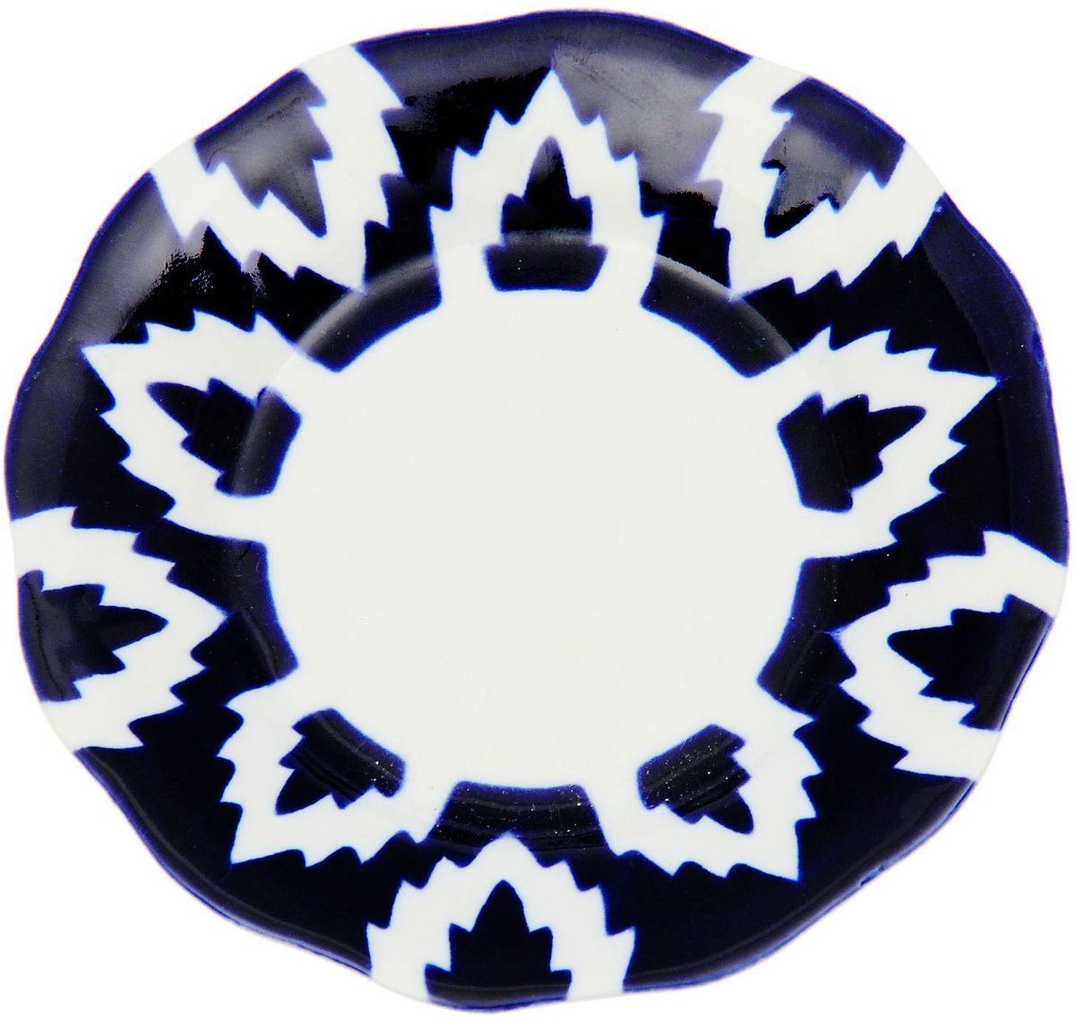 Тарелка Turon Porcelain Атлас, цвет: синий, белый, диаметр 12,5 см1625377Тарелка Turon Porcelain Атлас, выполненная из качественного фарфора, подойдет для повседневной и праздничной сервировки. Дополните стол текстилем и салфетками в тон, чтобы получить элегантное убранство с яркими акцентами.Национальная узбекская роспись Атлас имеет симметричный геометрический рисунок. Узоры, похожие на листья, выводятся тонкой кистью, фон заливается темно-синим кобальтом. Синий краситель при обжиге слегка растекается и придает контуру изображений голубой оттенок. Густая глазурь наносится толстым слоем, благодаря чему рисунок мерцает.Узбекская посуда известна всему миру уже более тысячи лет. Ей любовались царские особы, на ней подавали еду для шейхов и знатных персон. Формулы красок и глазури передаются из поколения в поколение. По сей день качественные расписные изделия продолжают восхищать совершенством и завораживающей красотой.