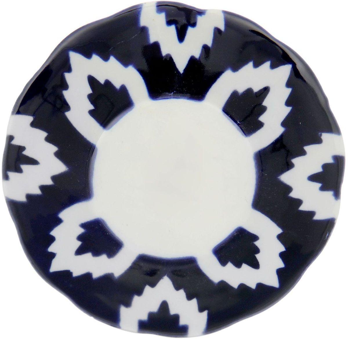 Тарелка Turon Porcelain Атлас, цвет: синий, белый, диаметр 13 см1625378Узбекская посуда известна всему миру уже более тысячи лет. Ей любовались царские особы, на ней подавали еду для шейхов и знатных персон. Формулы красок и глазури передаются из поколения в поколение. По сей день качественные расписные изделия продолжают восхищать совершенством и завораживающей красотой.Данный предмет подойдёт для повседневной и праздничной сервировки. Дополните стол текстилем и салфетками в тон, чтобы получить элегантное убранство с яркими акцентами.Национальная узбекская роспись «Атлас» имеет симметричный геометрический рисунок. Узоры, похожие на листья, выводятся тонкой кистью, фон заливается тёмно-синим кобальтом. Синий краситель при обжиге слегка растекается и придаёт контуру изображений голубой оттенок. Густая глазурь наносится толстым слоем, благодаря чему рисунок мерцает.