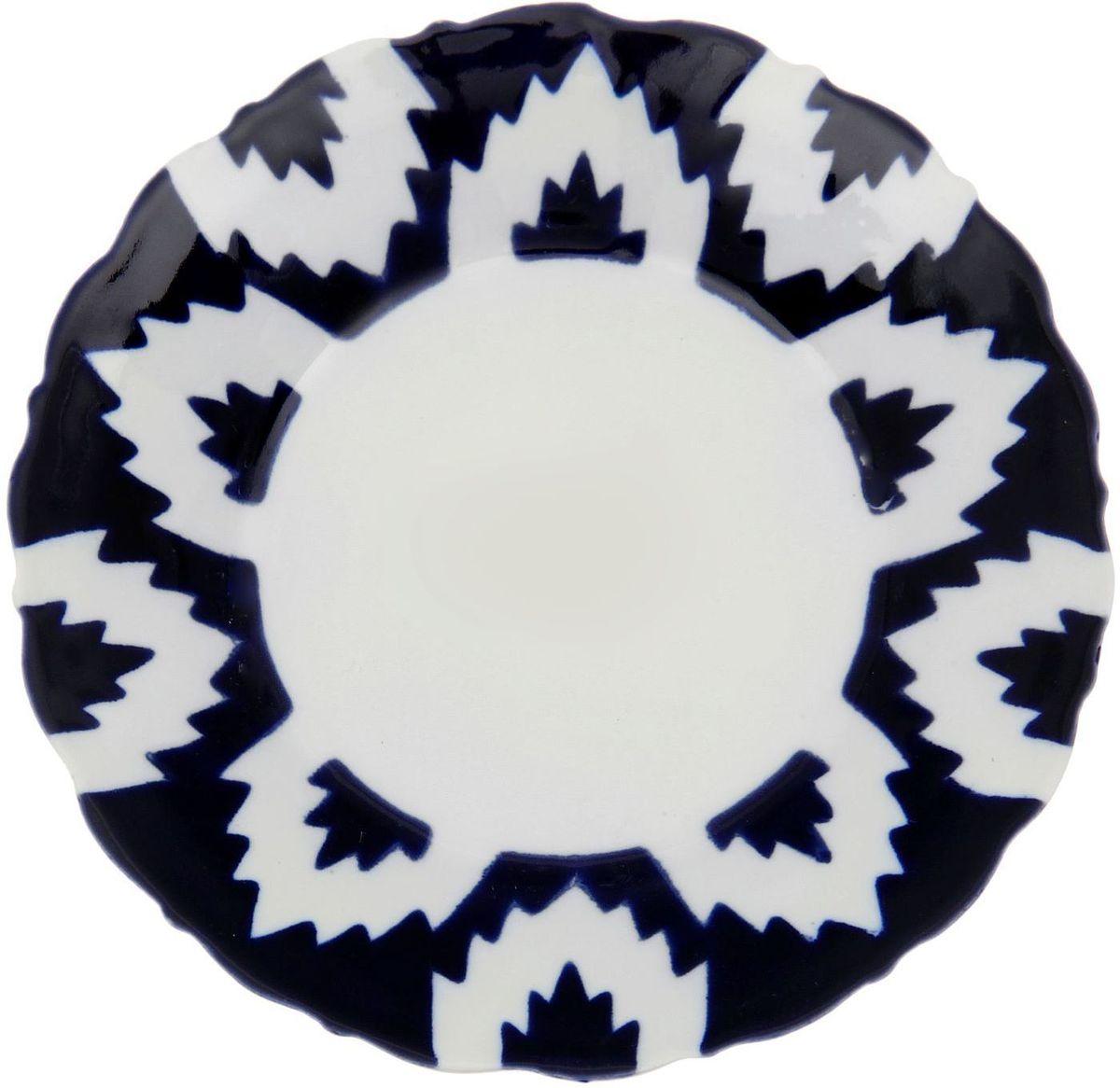 Тарелка Turon Porcelain Атлас, цвет: белый, синий, диаметр 16 см1625379Узбекская посуда известна всему миру уже более тысячи лет. Ей любовались царские особы, на ней подавали еду для шейхов и знатных персон. Формулы красок и глазури передаются из поколения в поколение. По сей день качественные расписные изделия продолжают восхищать совершенством и завораживающей красотой.Данный предмет подойдёт для повседневной и праздничной сервировки. Дополните стол текстилем и салфетками в тон, чтобы получить элегантное убранство с яркими акцентами.Национальная узбекская роспись «Атлас» имеет симметричный геометрический рисунок. Узоры, похожие на листья, выводятся тонкой кистью, фон заливается тёмно-синим кобальтом. Синий краситель при обжиге слегка растекается и придаёт контуру изображений голубой оттенок. Густая глазурь наносится толстым слоем, благодаря чему рисунок мерцает.