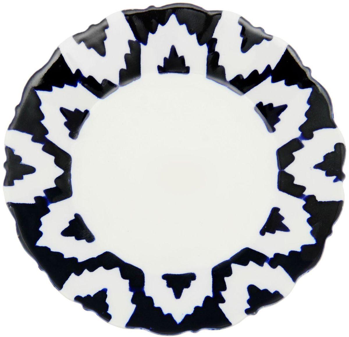 Тарелка Turon Porcelain Атлас, цвет: белый, синий, диаметр 17,5 см1625380Узбекская посуда известна всему миру уже более тысячи лет. Ей любовались царские особы, на ней подавали еду для шейхов и знатных персон. Формулы красок и глазури передаются из поколения в поколение. По сей день качественные расписные изделия продолжают восхищать совершенством и завораживающей красотой.Данный предмет подойдёт для повседневной и праздничной сервировки. Дополните стол текстилем и салфетками в тон, чтобы получить элегантное убранство с яркими акцентами.Национальная узбекская роспись «Атлас» имеет симметричный геометрический рисунок. Узоры, похожие на листья, выводятся тонкой кистью, фон заливается тёмно-синим кобальтом. Синий краситель при обжиге слегка растекается и придаёт контуру изображений голубой оттенок. Густая глазурь наносится толстым слоем, благодаря чему рисунок мерцает.