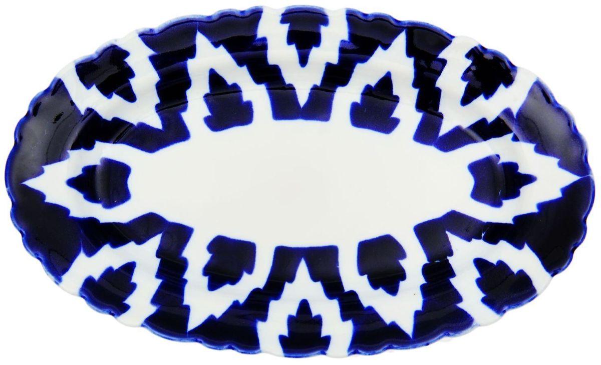 Тарелка Turon Porcelain Атлас, цвет: синий, белый, 23 х 14 см1625383Узбекская посуда известна всему миру уже более тысячи лет. Ей любовались царские особы, на ней подавали еду для шейхов и знатных персон. Формулы красок и глазури передаются из поколения в поколение. По сей день качественные расписные изделия продолжают восхищать совершенством и завораживающей красотой.Данный предмет подойдёт для повседневной и праздничной сервировки. Дополните стол текстилем и салфетками в тон, чтобы получить элегантное убранство с яркими акцентами.Национальная узбекская роспись «Атлас» имеет симметричный геометрический рисунок. Узоры, похожие на листья, выводятся тонкой кистью, фон заливается тёмно-синим кобальтом. Синий краситель при обжиге слегка растекается и придаёт контуру изображений голубой оттенок. Густая глазурь наносится толстым слоем, благодаря чему рисунок мерцает.