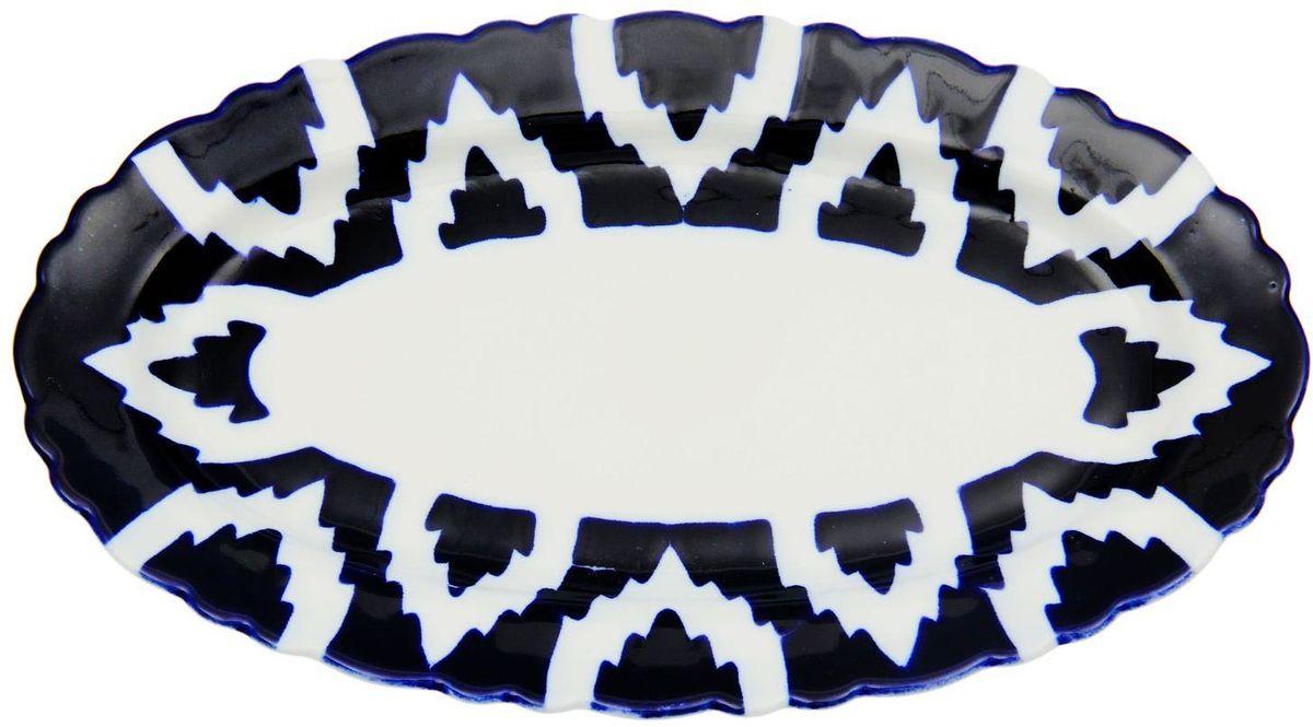 Тарелка Turon Porcelain Атлас, цвет: синий, белый, 30 х 17 см1625384Узбекская посуда известна всему миру уже более тысячи лет. Ей любовались царские особы, на ней подавали еду для шейхов и знатных персон. Формулы красок и глазури передаются из поколения в поколение. По сей день качественные расписные изделия продолжают восхищать совершенством и завораживающей красотой.Данный предмет подойдёт для повседневной и праздничной сервировки. Дополните стол текстилем и салфетками в тон, чтобы получить элегантное убранство с яркими акцентами.Национальная узбекская роспись «Атлас» имеет симметричный геометрический рисунок. Узоры, похожие на листья, выводятся тонкой кистью, фон заливается тёмно-синим кобальтом. Синий краситель при обжиге слегка растекается и придаёт контуру изображений голубой оттенок. Густая глазурь наносится толстым слоем, благодаря чему рисунок мерцает.
