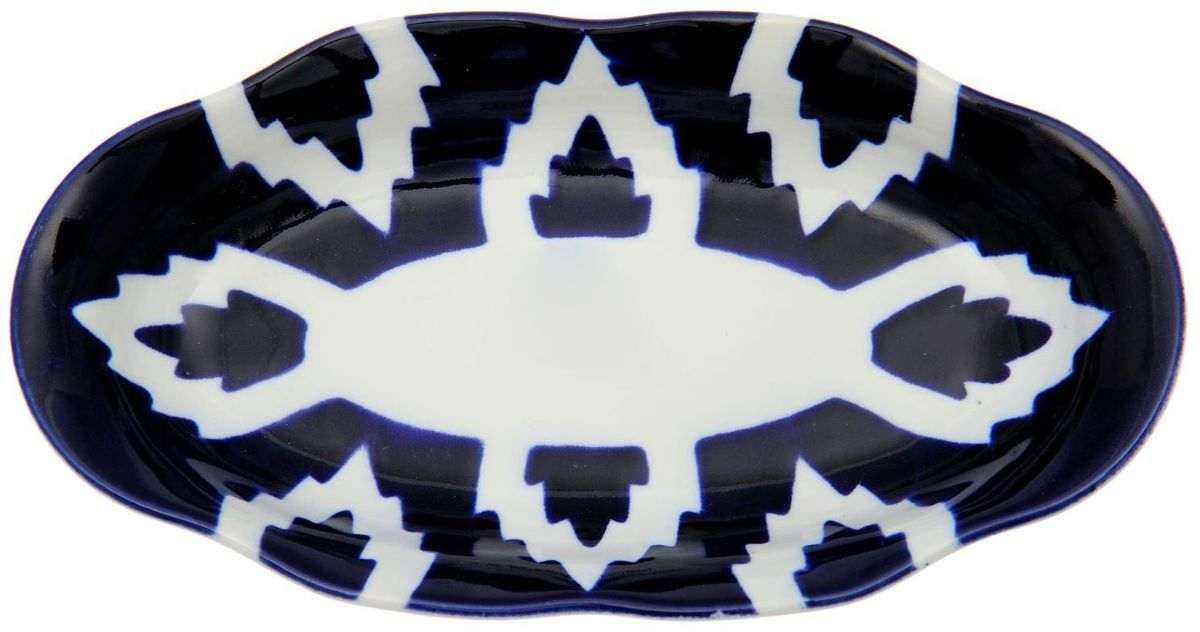 Тарелка Turon Porcelain Атлас, цвет: белый, синий, 18 х 10 см1625387Узбекская посуда известна всему миру уже более тысячи лет. Ей любовались царские особы, на ней подавали еду для шейхов и знатных персон. Формулы красок и глазури передаются из поколения в поколение. По сей день качественные расписные изделия продолжают восхищать совершенством и завораживающей красотой.Данный предмет подойдёт для повседневной и праздничной сервировки. Дополните стол текстилем и салфетками в тон, чтобы получить элегантное убранство с яркими акцентами.Национальная узбекская роспись «Атлас» имеет симметричный геометрический рисунок. Узоры, похожие на листья, выводятся тонкой кистью, фон заливается тёмно-синим кобальтом. Синий краситель при обжиге слегка растекается и придаёт контуру изображений голубой оттенок. Густая глазурь наносится толстым слоем, благодаря чему рисунок мерцает.