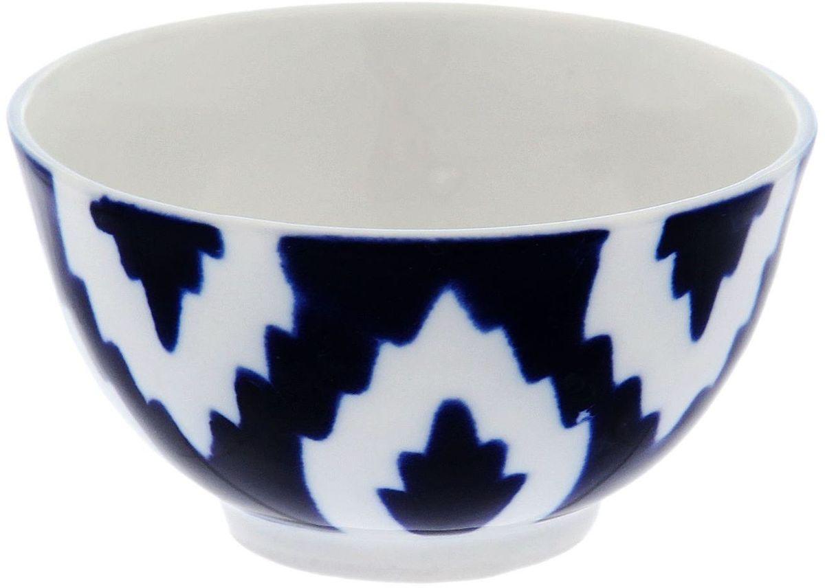 Пиала Turon Porcelain Атлас, цвет: синий, белый, 100 мл1625389Узбекская посуда известна всему миру уже более тысячи лет. Ей любовались царские особы, на ней подавали еду для шейхов и знатных персон. Формулы красок и глазури передаются из поколения в поколение. По сей день качественные расписные изделия продолжают восхищать совершенством и завораживающей красотой. Пиала Turon Porcelain Атлас подойдет для повседневной и праздничной сервировки. Дополните стол текстилем и салфетками в тон, чтобы получить элегантное убранство с яркими акцентами.Национальная узбекская роспись Атлас имеет симметричный геометрический рисунок. Узоры, похожие на листья, выводятся тонкой кистью, фон заливается темно-синим кобальтом. Синий краситель при обжиге слегка растекается и придает контуру изображений голубой оттенок. Густая глазурь наносится толстым слоем, благодаря чему рисунок мерцает.