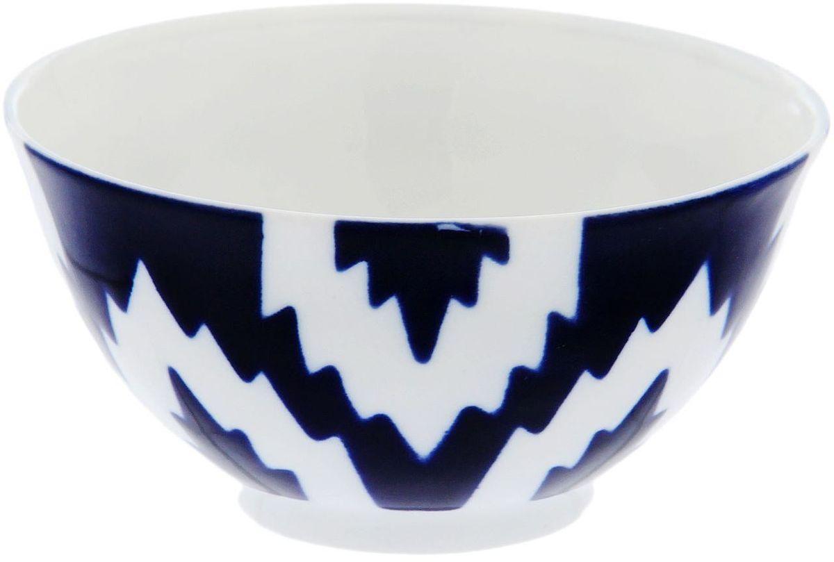 Пиала Turon Porcelain Атлас, цвет: синий, белый, 150 мл1625390Узбекская посуда известна всему миру уже более тысячи лет. Ей любовались царские особы, на ней подавали еду для шейхов и знатных персон. Формулы красок и глазури передаются из поколения в поколение. По сей день качественные расписные изделия продолжают восхищать совершенством и завораживающей красотой.Данный предмет подойдёт для повседневной и праздничной сервировки. Дополните стол текстилем и салфетками в тон, чтобы получить элегантное убранство с яркими акцентами.Национальная узбекская роспись «Атлас» имеет симметричный геометрический рисунок. Узоры, похожие на листья, выводятся тонкой кистью, фон заливается тёмно-синим кобальтом. Синий краситель при обжиге слегка растекается и придаёт контуру изображений голубой оттенок. Густая глазурь наносится толстым слоем, благодаря чему рисунок мерцает.