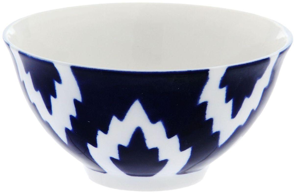 Пиала Turon Porcelain Атлас, цвет: синий, белый, 250 млIMB0304A-A194/NALУзбекская посуда известна всему миру уже более тысячи лет. Ей любовались царские особы, на ней подавали еду для шейхов и знатных персон. Формулы красок и глазури передаются из поколения в поколение. По сей день качественные расписные изделия продолжают восхищать совершенством и завораживающей красотой. Пиала Turon Porcelain Атлас подойдет для повседневной и праздничной сервировки. Дополните стол текстилем и салфетками в тон, чтобы получить элегантное убранство с яркими акцентами.Национальная узбекская роспись Атлас имеет симметричный геометрический рисунок. Узоры, похожие на листья, выводятся тонкой кистью, фон заливается темно-синим кобальтом. Синий краситель при обжиге слегка растекается и придает контуру изображений голубой оттенок. Густая глазурь наносится толстым слоем, благодаря чему рисунок мерцает.