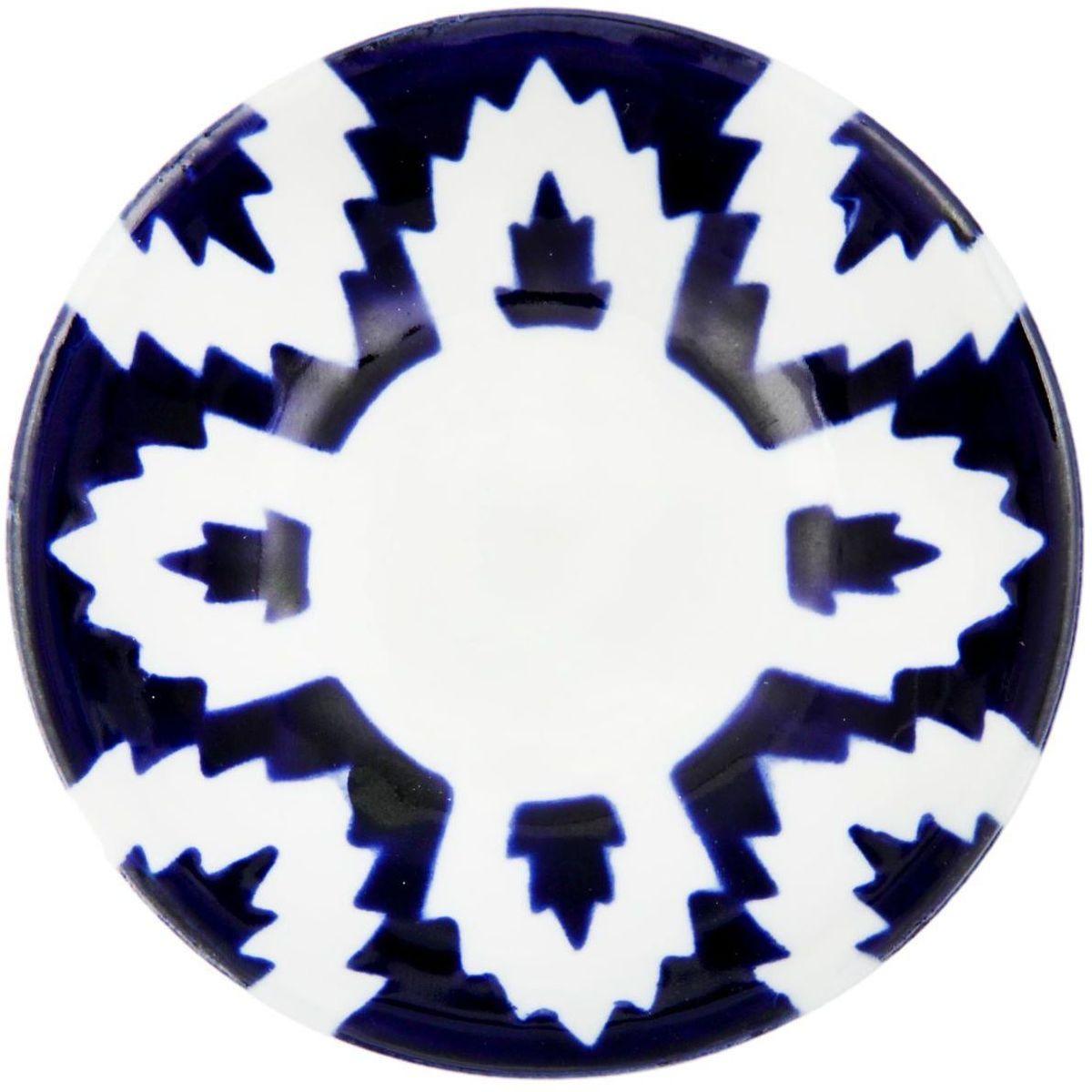 Икорница Turon Porcelain Атлас, цвет: белый, синий, диаметр 10,5 см1625393Узбекская посуда известна всему миру уже более тысячи лет. Ей любовались царские особы, на ней подавали еду для шейхов и знатных персон. Формулы красок и глазури передаются из поколения в поколение. По сей день качественные расписные изделия продолжают восхищать совершенством и завораживающей красотой. Икорница Turon Porcelain Атлас подойдет для повседневной и праздничной сервировки. Дополните стол текстилем и салфетками в тон, чтобы получить элегантное убранство с яркими акцентами.Национальная узбекская роспись Атлас имеет симметричный геометрический рисунок. Узоры, похожие на листья, выводятся тонкой кистью, фон заливается темно-синим кобальтом. Синий краситель при обжиге слегка растекается и придает контуру изображений голубой оттенок. Густая глазурь наносится толстым слоем, благодаря чему рисунок мерцает.