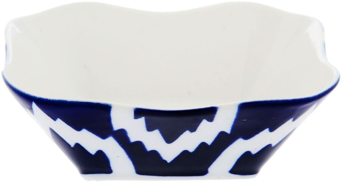Салатница Turon Porcelain Атлас, цвет: синий, белый, диаметр 14 см1625396Узбекская посуда известна всему миру уже более тысячи лет. Ей любовались царские особы, на ней подавали еду для шейхов и знатных персон. Формулы красок и глазури передаются из поколения в поколение. По сей день качественные расписные изделия продолжают восхищать совершенством и завораживающей красотой.Данный предмет подойдёт для повседневной и праздничной сервировки. Дополните стол текстилем и салфетками в тон, чтобы получить элегантное убранство с яркими акцентами.Национальная узбекская роспись «Атлас» имеет симметричный геометрический рисунок. Узоры, похожие на листья, выводятся тонкой кистью, фон заливается тёмно-синим кобальтом. Синий краситель при обжиге слегка растекается и придаёт контуру изображений голубой оттенок. Густая глазурь наносится толстым слоем, благодаря чему рисунок мерцает.