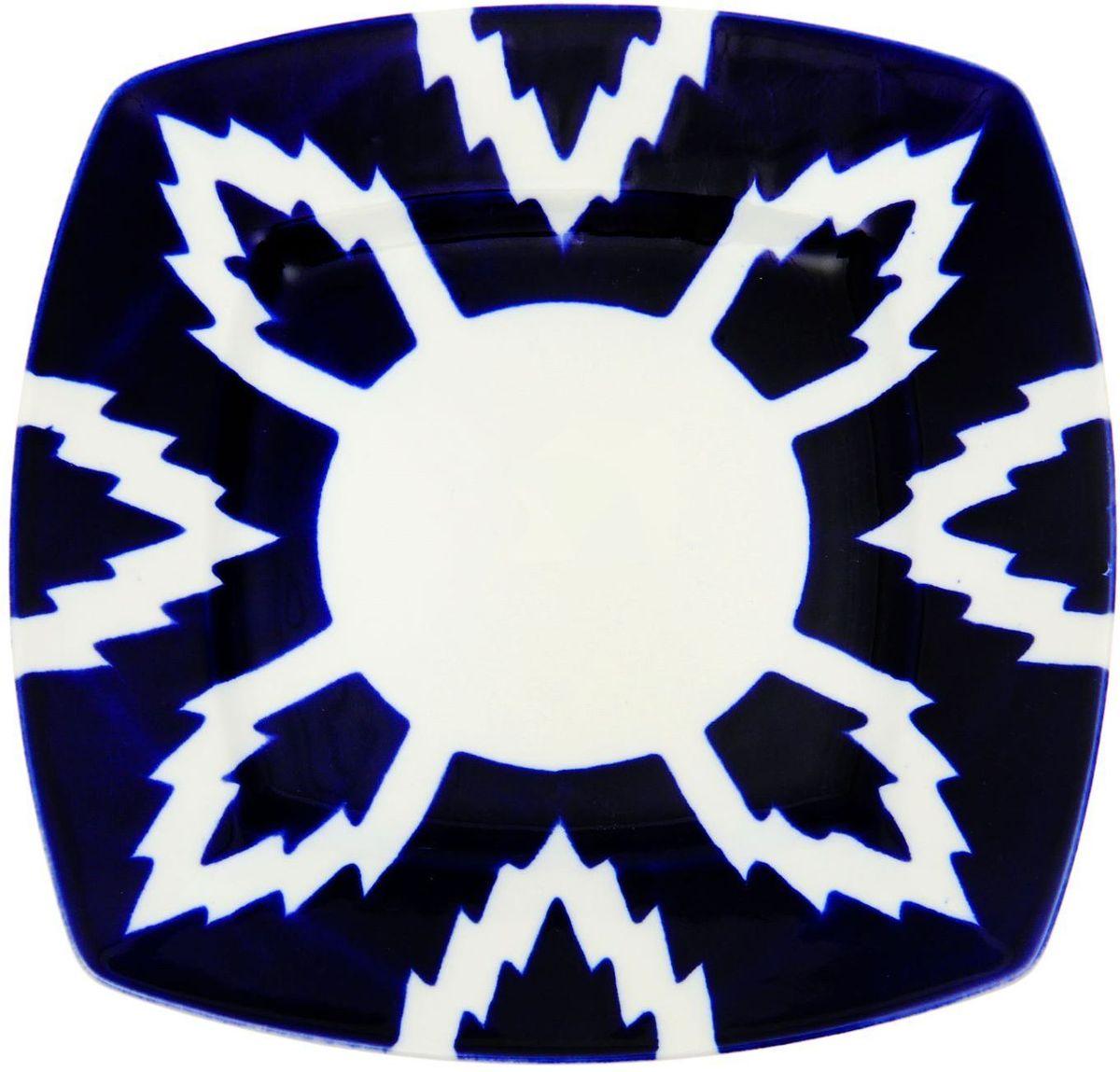Тарелка Turon Porcelain Атлас, цвет: синий, белый, 20 х 20 см1625400Узбекская посуда известна всему миру уже более тысячи лет. Ей любовались царские особы, на ней подавали еду для шейхов и знатных персон. Формулы красок и глазури передаются из поколения в поколение. По сей день качественные расписные изделия продолжают восхищать совершенством и завораживающей красотой.Данный предмет подойдёт для повседневной и праздничной сервировки. Дополните стол текстилем и салфетками в тон, чтобы получить элегантное убранство с яркими акцентами.Национальная узбекская роспись «Атлас» имеет симметричный геометрический рисунок. Узоры, похожие на листья, выводятся тонкой кистью, фон заливается тёмно-синим кобальтом. Синий краситель при обжиге слегка растекается и придаёт контуру изображений голубой оттенок. Густая глазурь наносится толстым слоем, благодаря чему рисунок мерцает.
