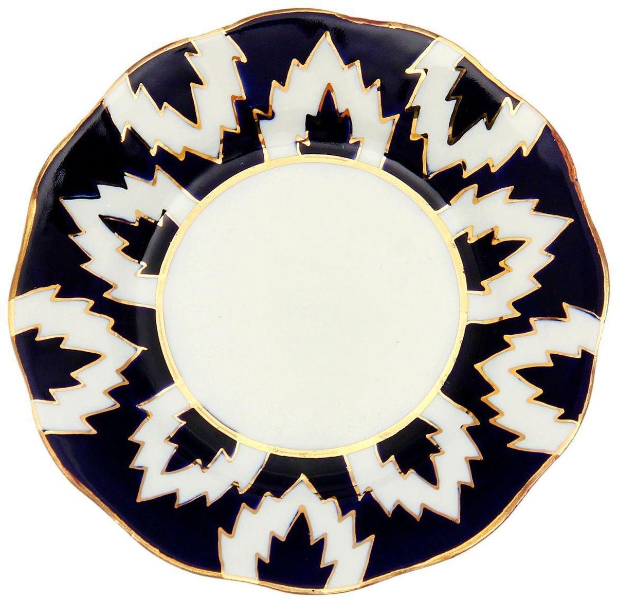 Тарелка Turon Porcelain Атлас, цвет: синий, белый, золотистый, диаметр 12,5 см1625401Узбекская посуда известна всему миру уже более тысячи лет. Ей любовались царские особы, на ней подавали еду для шейхов и знатных персон. Формулы красок и глазури передаются из поколения в поколение. По сей день качественные расписные изделия продолжают восхищать совершенством и завораживающей красотой.Данный предмет подойдёт для повседневной и праздничной сервировки. Дополните стол текстилем и салфетками в тон, чтобы получить элегантное убранство с яркими акцентами.Национальная узбекская роспись «Атлас» имеет симметричный геометрический рисунок. Узоры, похожие на листья, выводятся тонкой кистью, фон заливается тёмно-синим кобальтом. Синий краситель при обжиге слегка растекается и придаёт контуру изображений голубой оттенок. Густая глазурь наносится толстым слоем, благодаря чему рисунок мерцает.