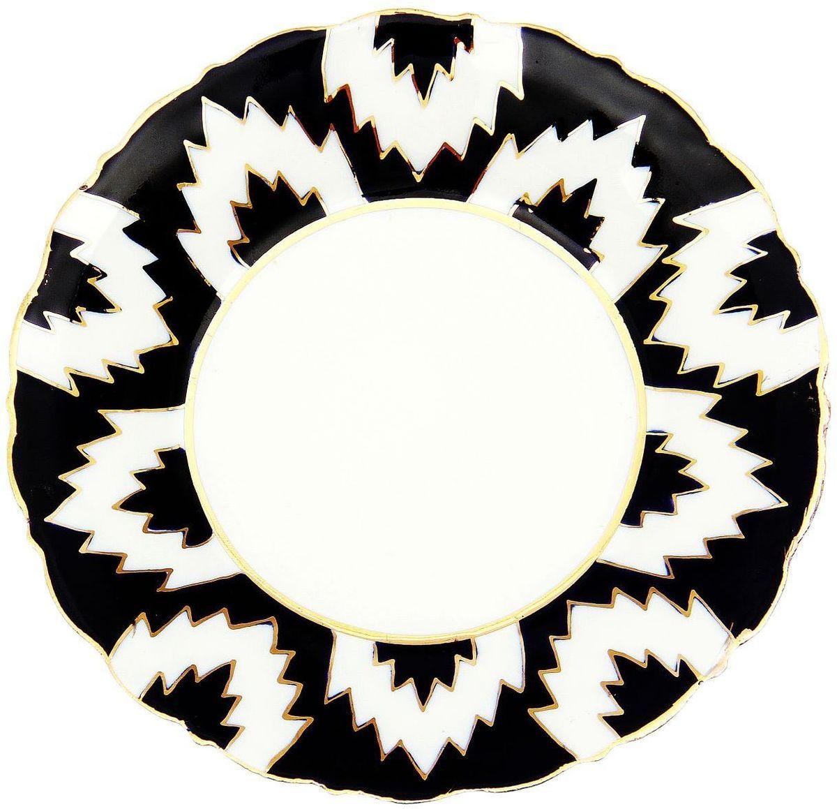 Тарелка Turon Porcelain Атлас, цвет: белый, синий, золотистый, диаметр 16 см1625403Узбекская посуда известна всему миру уже более тысячи лет. Ей любовались царские особы, на ней подавали еду для шейхов и знатных персон. Формулы красок и глазури передаются из поколения в поколение. По сей день качественные расписные изделия продолжают восхищать совершенством и завораживающей красотой.Данный предмет подойдёт для повседневной и праздничной сервировки. Дополните стол текстилем и салфетками в тон, чтобы получить элегантное убранство с яркими акцентами.Национальная узбекская роспись «Атлас» имеет симметричный геометрический рисунок. Узоры, похожие на листья, выводятся тонкой кистью, фон заливается тёмно-синим кобальтом. Синий краситель при обжиге слегка растекается и придаёт контуру изображений голубой оттенок. Густая глазурь наносится толстым слоем, благодаря чему рисунок мерцает.