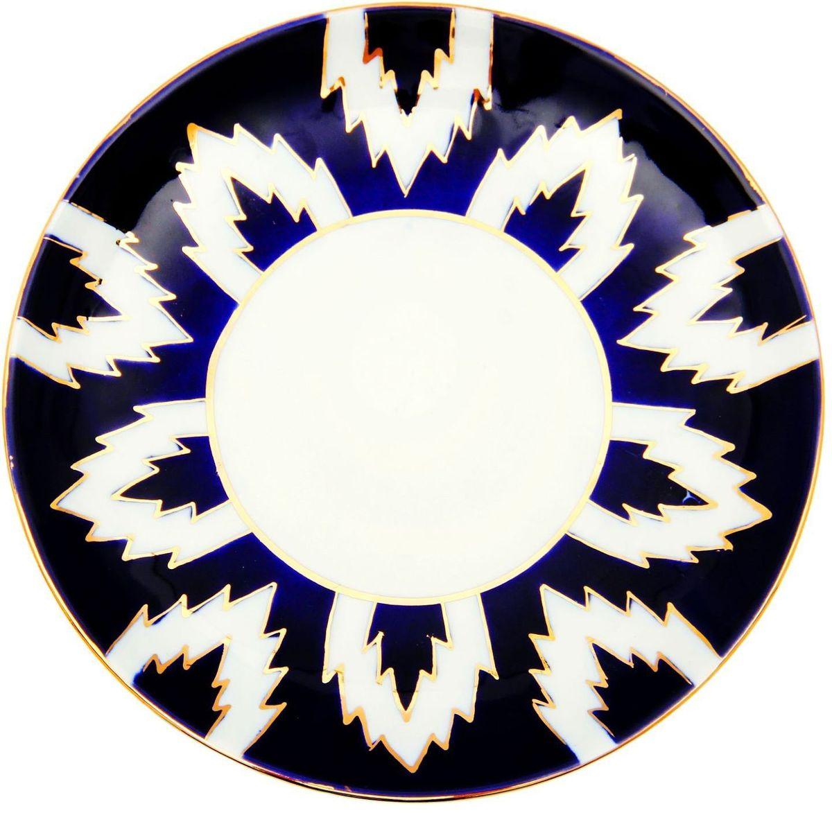 Тарелка Turon Porcelain Атлас, цвет: белый, синий, золотистый, диаметр 19,5 см1625405Тарелка Turon Porcelain Атлас, выполненная из качественного фарфора, подойдет для повседневной и праздничной сервировки. Дополните стол текстилем и салфетками в тон, чтобы получить элегантное убранство с яркими акцентами. Национальная узбекская роспись Атлас имеет симметричный геометрический рисунок. Узоры, похожие на листья, выводятся тонкой кистью, фон заливается темно-синим кобальтом. Синий краситель при обжиге слегка растекается и придает контуру изображений голубой оттенок. Густая глазурь наносится толстым слоем, благодаря чему рисунок мерцает. Узбекская посуда известна всему миру уже более тысячи лет. Ей любовались царские особы, на ней подавали еду для шейхов и знатных персон. Формулы красок и глазури передаются из поколения в поколение. По сей день качественные расписные изделия продолжают восхищать совершенством и завораживающей красотой.