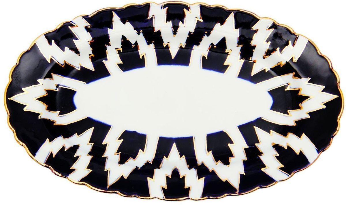 Тарелка Turon Porcelain Атлас, цвет: синий, белый, золотистый, 23 х 14 см1625407Тарелка Turon Porcelain Атлас, выполненная из качественного фарфора, подойдет для повседневной и праздничной сервировки. Дополните стол текстилем и салфетками в тон, чтобы получить элегантное убранство с яркими акцентами. Национальная узбекская роспись Атлас имеет симметричный геометрический рисунок. Узоры, похожие на листья, выводятся тонкой кистью, фон заливается темно-синим кобальтом. Синий краситель при обжиге слегка растекается и придает контуру изображений голубой оттенок. Густая глазурь наносится толстым слоем, благодаря чему рисунок мерцает. Узбекская посуда известна всему миру уже более тысячи лет. Ей любовались царские особы, на ней подавали еду для шейхов и знатных персон. Формулы красок и глазури передаются из поколения в поколение. По сей день качественные расписные изделия продолжают восхищать совершенством и завораживающей красотой.