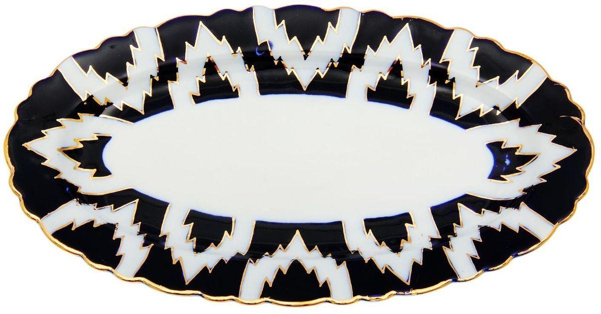 Тарелка Turon Porcelain Атлас, цвет: синий, белый, золотистый, 30 х 17 см1625408Тарелка Turon Porcelain Атлас, выполненная из качественного фарфора, подойдет для повседневной и праздничной сервировки. Дополните стол текстилем и салфетками в тон, чтобы получить элегантное убранство с яркими акцентами. Национальная узбекская роспись Атлас имеет симметричный геометрический рисунок. Узоры, похожие на листья, выводятся тонкой кистью, фон заливается темно-синим кобальтом. Синий краситель при обжиге слегка растекается и придает контуру изображений голубой оттенок. Густая глазурь наносится толстым слоем, благодаря чему рисунок мерцает. Узбекская посуда известна всему миру уже более тысячи лет. Ей любовались царские особы, на ней подавали еду для шейхов и знатных персон. Формулы красок и глазури передаются из поколения в поколение. По сей день качественные расписные изделия продолжают восхищать совершенством и завораживающей красотой.