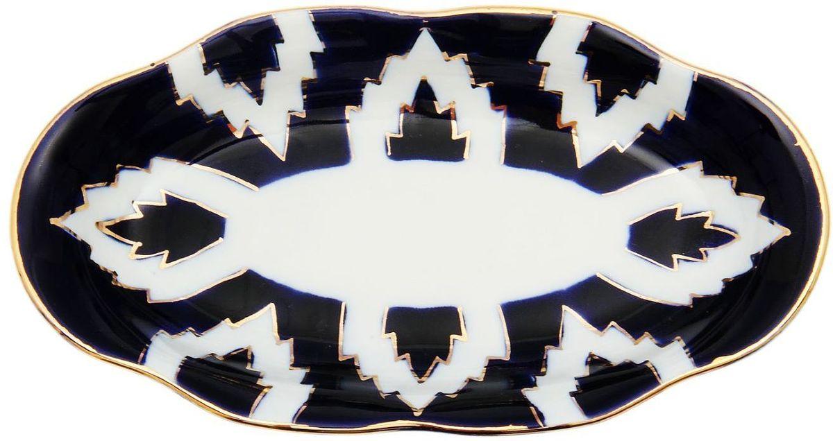 Тарелка Turon Porcelain Атлас, цвет: белый, синий, золотистый, 18 х 10 см1625411Тарелка Turon Porcelain Атлас, выполненная из качественного фарфора, подойдет для повседневной и праздничной сервировки. Дополните стол текстилем и салфетками в тон, чтобы получить элегантное убранство с яркими акцентами. Национальная узбекская роспись Атлас имеет симметричный геометрический рисунок. Узоры, похожие на листья, выводятся тонкой кистью, фон заливается темно-синим кобальтом. Синий краситель при обжиге слегка растекается и придает контуру изображений голубой оттенок. Густая глазурь наносится толстым слоем, благодаря чему рисунок мерцает. Узбекская посуда известна всему миру уже более тысячи лет. Ей любовались царские особы, на ней подавали еду для шейхов и знатных персон. Формулы красок и глазури передаются из поколения в поколение. По сей день качественные расписные изделия продолжают восхищать совершенством и завораживающей красотой.