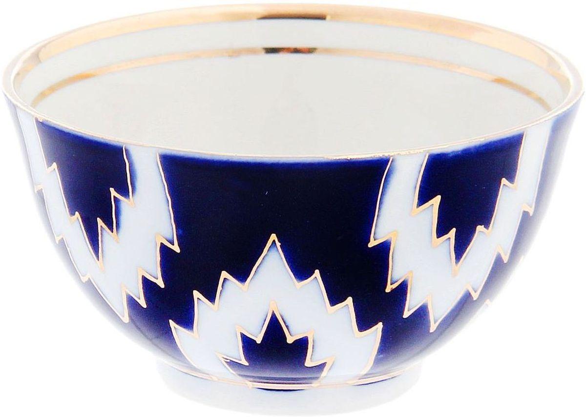 Пиала Turon Porcelain Атлас, цвет: синий, белый, золотистый, 100 мл1625413Узбекская посуда известна всему миру уже более тысячи лет. Ей любовались царские особы, на ней подавали еду для шейхов и знатных персон. Формулы красок и глазури передаются из поколения в поколение. По сей день качественные расписные изделия продолжают восхищать совершенством и завораживающей красотой.Данный предмет подойдёт для повседневной и праздничной сервировки. Дополните стол текстилем и салфетками в тон, чтобы получить элегантное убранство с яркими акцентами.Национальная узбекская роспись «Атлас» имеет симметричный геометрический рисунок. Узоры, похожие на листья, выводятся тонкой кистью, фон заливается тёмно-синим кобальтом. Синий краситель при обжиге слегка растекается и придаёт контуру изображений голубой оттенок. Густая глазурь наносится толстым слоем, благодаря чему рисунок мерцает.