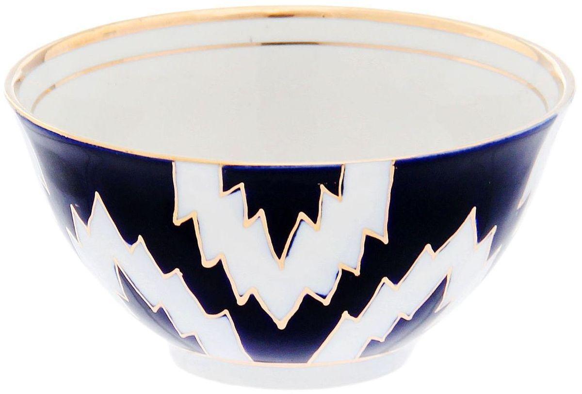 Пиала Turon Porcelain Атлас, цвет: синий, белый, золотистый, 150 мл1625414Узбекская посуда известна всему миру уже более тысячи лет. Ей любовались царские особы, на ней подавали еду для шейхов и знатных персон. Формулы красок и глазури передаются из поколения в поколение. По сей день качественные расписные изделия продолжают восхищать совершенством и завораживающей красотой.Данный предмет подойдёт для повседневной и праздничной сервировки. Дополните стол текстилем и салфетками в тон, чтобы получить элегантное убранство с яркими акцентами.Национальная узбекская роспись Атлас имеет симметричный геометрический рисунок. Узоры, похожие на листья, выводятся тонкой кистью, фон заливается тёмно-синим кобальтом. Синий краситель при обжиге слегка растекается и придаёт контуру изображений голубой оттенок. Густая глазурь наносится толстым слоем, благодаря чему рисунок мерцает.
