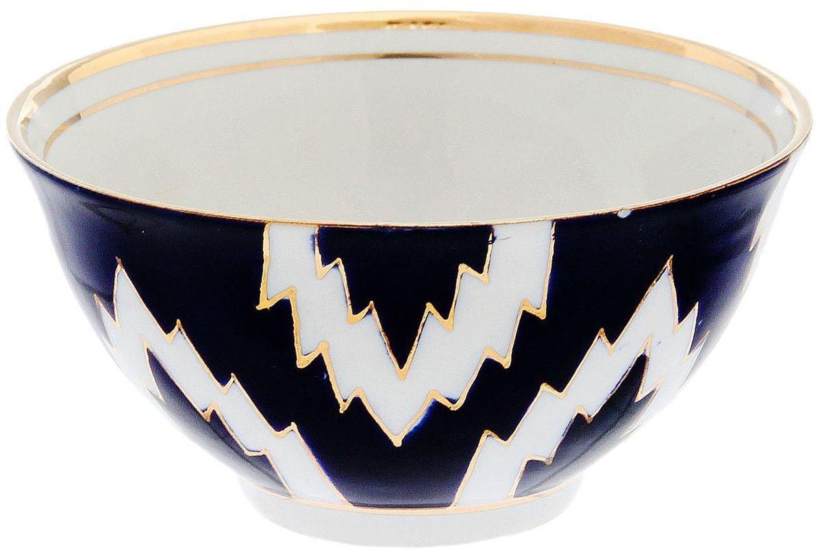 Пиала Turon Porcelain Атлас, цвет: синий, белый, золотистый, 250 мл1625415Узбекская посуда известна всему миру уже более тысячи лет. Ей любовались царские особы, на ней подавали еду для шейхов и знатных персон. Формулы красок и глазури передаются из поколения в поколение. По сей день качественные расписные изделия продолжают восхищать совершенством и завораживающей красотой.Данный предмет подойдёт для повседневной и праздничной сервировки. Дополните стол текстилем и салфетками в тон, чтобы получить элегантное убранство с яркими акцентами.Национальная узбекская роспись «Атлас» имеет симметричный геометрический рисунок. Узоры, похожие на листья, выводятся тонкой кистью, фон заливается тёмно-синим кобальтом. Синий краситель при обжиге слегка растекается и придаёт контуру изображений голубой оттенок. Густая глазурь наносится толстым слоем, благодаря чему рисунок мерцает.