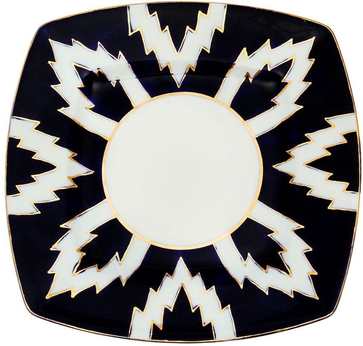 Тарелка Turon Porcelain Атлас, цвет: синий, белый, золотистый, 20 х 20 см1625424Тарелка Turon Porcelain Атлас, выполненная из качественного фарфора, подойдет для повседневной и праздничной сервировки. Дополните стол текстилем и салфетками в тон, чтобы получить элегантное убранство с яркими акцентами. Национальная узбекская роспись Атлас имеет симметричный геометрический рисунок. Узоры, похожие на листья, выводятся тонкой кистью, фон заливается темно-синим кобальтом. Синий краситель при обжиге слегка растекается и придает контуру изображений голубой оттенок. Густая глазурь наносится толстым слоем, благодаря чему рисунок мерцает. Узбекская посуда известна всему миру уже более тысячи лет. Ей любовались царские особы, на ней подавали еду для шейхов и знатных персон. Формулы красок и глазури передаются из поколения в поколение. По сей день качественные расписные изделия продолжают восхищать совершенством и завораживающей красотой.