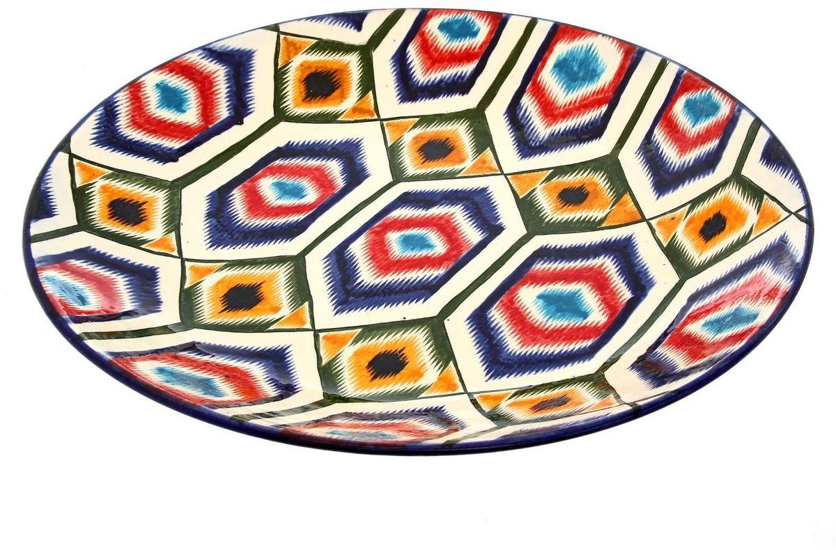 Ляган Риштанская керамика Атлас, диаметр 41 см2245468Узбекская посуда известна всему миру уже более тысячи лет. Ей любовались царские особы, на ней подавали еду для шейхов и знатных персон. Формулы красок и глазури передаются из поколения в поколение. По сей день качественные расписные изделия продолжают восхищать совершенством и завораживающей красотой.Данный предмет подойдёт для повседневной и праздничной сервировки. Дополните стол текстилем и салфетками в тон, чтобы получить элегантное убранство с яркими акцентами.Национальная узбекская роспись «Атлас» имеет симметричный геометрический рисунок. Узоры, похожие на листья, выводятся тонкой кистью, фон заливается тёмно-синим кобальтом. Синий краситель при обжиге слегка растекается и придаёт контуру изображений голубой оттенок. Густая глазурь наносится толстым слоем, благодаря чему рисунок мерцает.