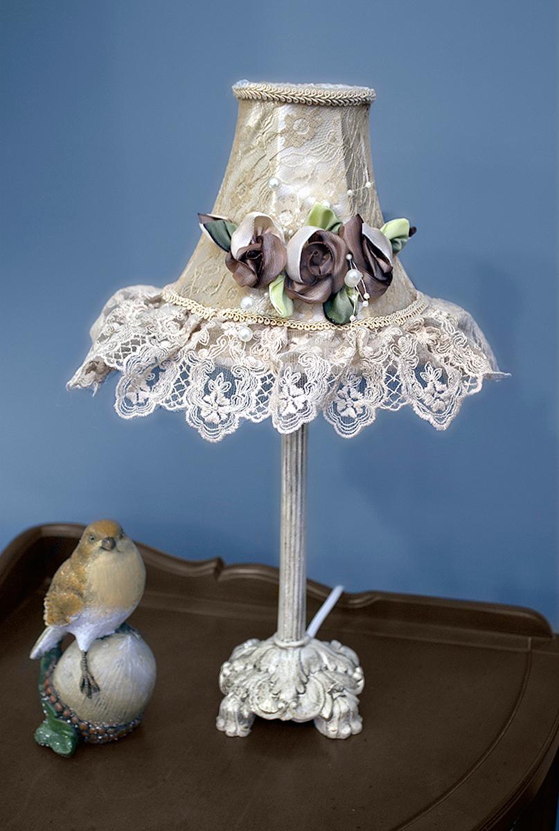 """Лампа настольная ручной работы """"Estro"""" станет украшением вашей комнаты и оригинально дополнит интерьер. Такой светильник отлично подойдет для освещения кабинета, спальни или гостиной. Лампа выполнена из бежевого металла. Абажур лампы изготовлен из полиэстера и дополнен текстильным украшением.К светильнику предусмотрен цоколь Е14 для лампы мощностью 40 Вт.Высота лампы: 40 см."""