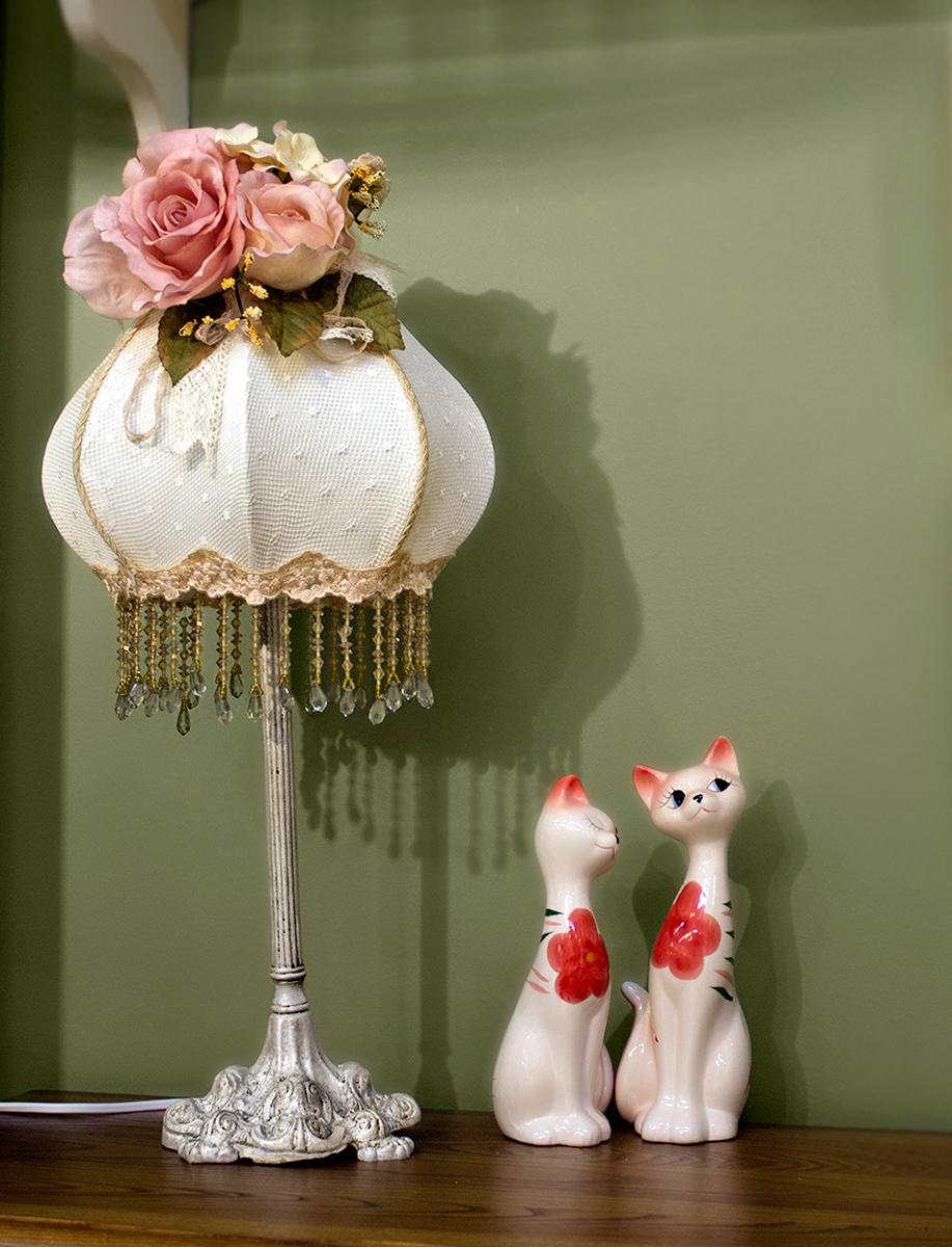 """Лампа настольная ручной работы """"Estro"""" станет украшением вашей комнаты и оригинально дополнит интерьер. Такой светильник отлично подойдет для освещения кабинета, спальни или гостиной. Лампа выполнена из бежевого металла. Абажур лампы изготовлен из полиэстера и дополнен текстильным украшением.К светильнику предусмотрен цоколь Е14 для лампы мощностью 40 Вт.Высота лампы: 50 см."""