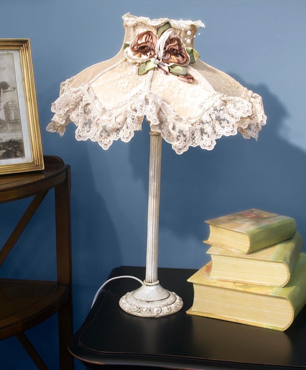 """Лампа настольная ручной работы """"Estro"""" станет украшением вашей комнаты и оригинально дополнит интерьер. Такой светильник отлично подойдет для освещения кабинета, спальни или гостиной. Лампа выполнена из бежевого металла. Абажур лампы изготовлен из полиэстера и дополнен текстильным украшением.К светильнику предусмотрен цоколь Е14 для лампы мощностью 40 Вт.Высота лампы: 62 см."""